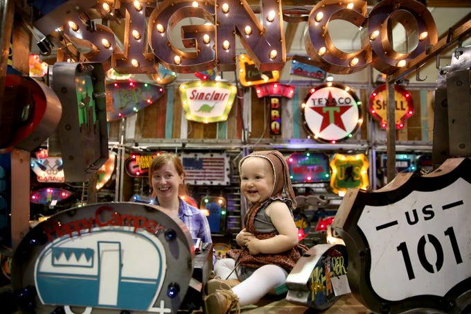Evelyn Felty, 15 months, laughs on the counter as her mom, Julia Felty, watches over the family's booth during The Great Junk Hunt, a traveling vintage market, at the Oregon State Fairgrounds in Salem on April 13, 2019.
