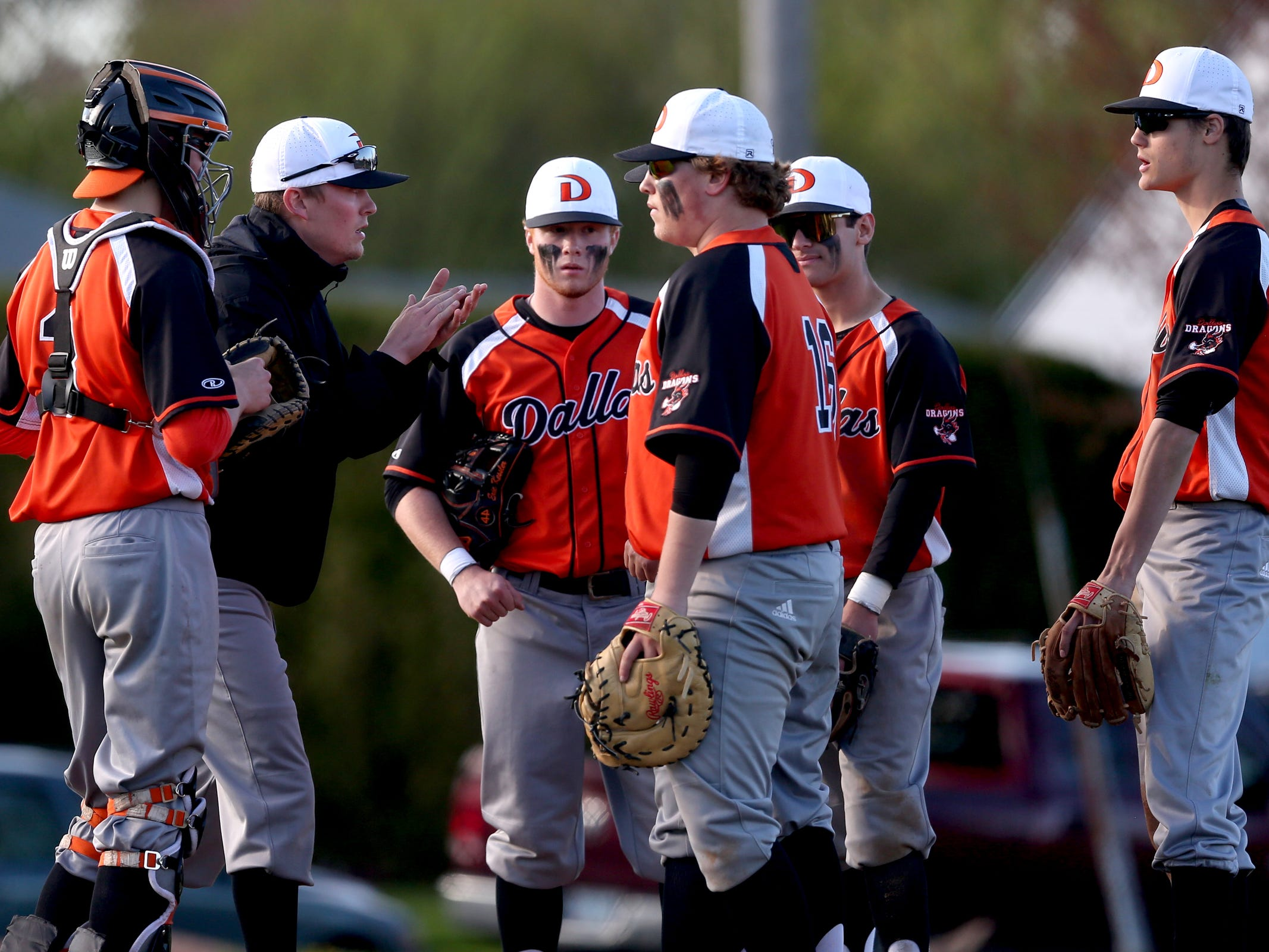 Dallas head coach Keeton Luther talks to his team on the mound in the Dallas vs. North Salem baseball game in Salem on April 12, 2019.