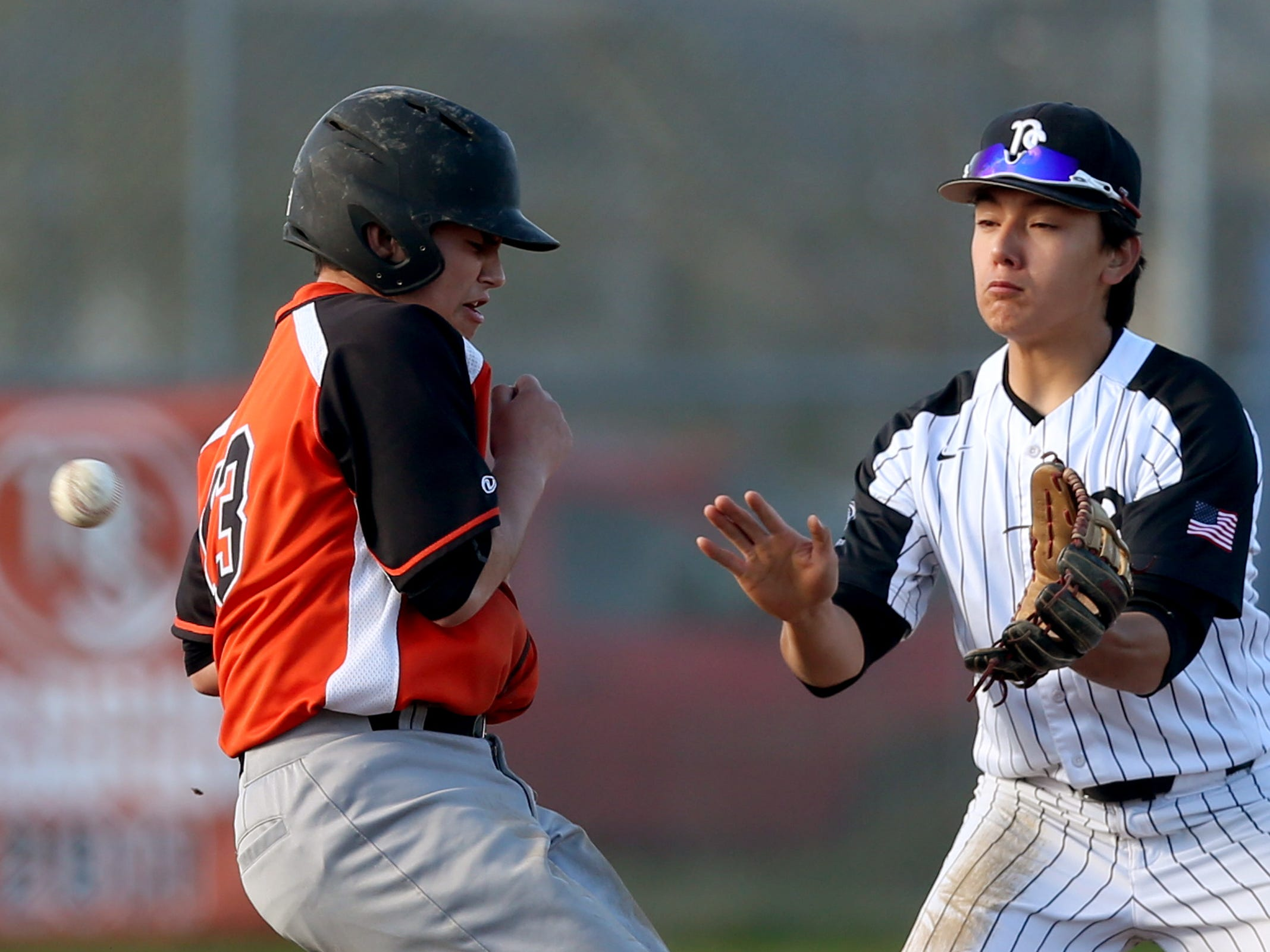 North Salem's William Tsukamaki (8) tries to make a catch to get a Dallas player out at second in the Dallas vs. North Salem baseball game in Salem on April 12, 2019.