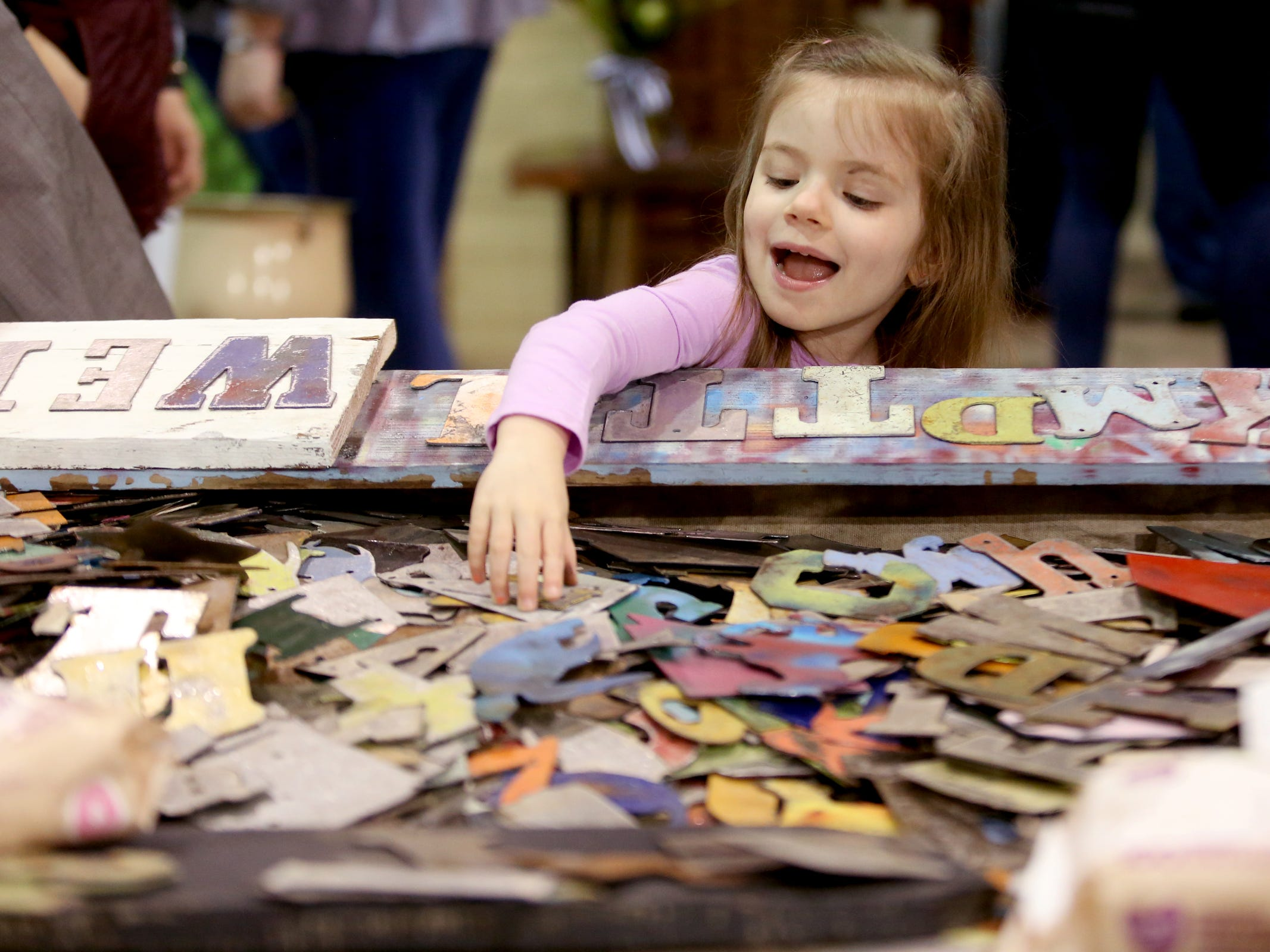 McKenzie Moreland, 4, of Eugene, looks through letters as her mom makes a custom sign during The Great Junk Hunt, a traveling vintage market, at the Oregon State Fairgrounds in Salem on April 13, 2019.