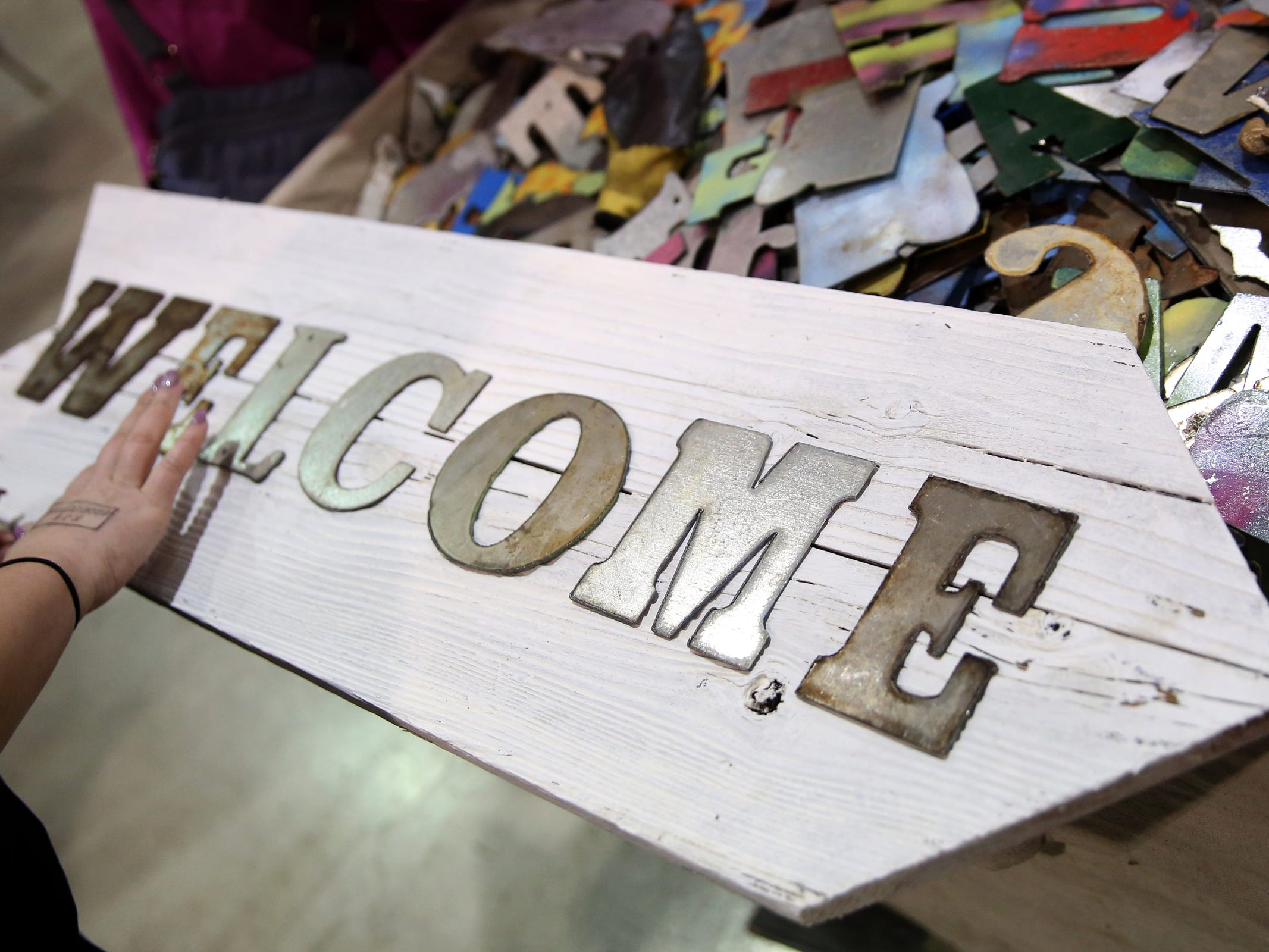People mix and match metal letters to create custom signs during The Great Junk Hunt, a traveling vintage market, at the Oregon State Fairgrounds in Salem on April 13, 2019.
