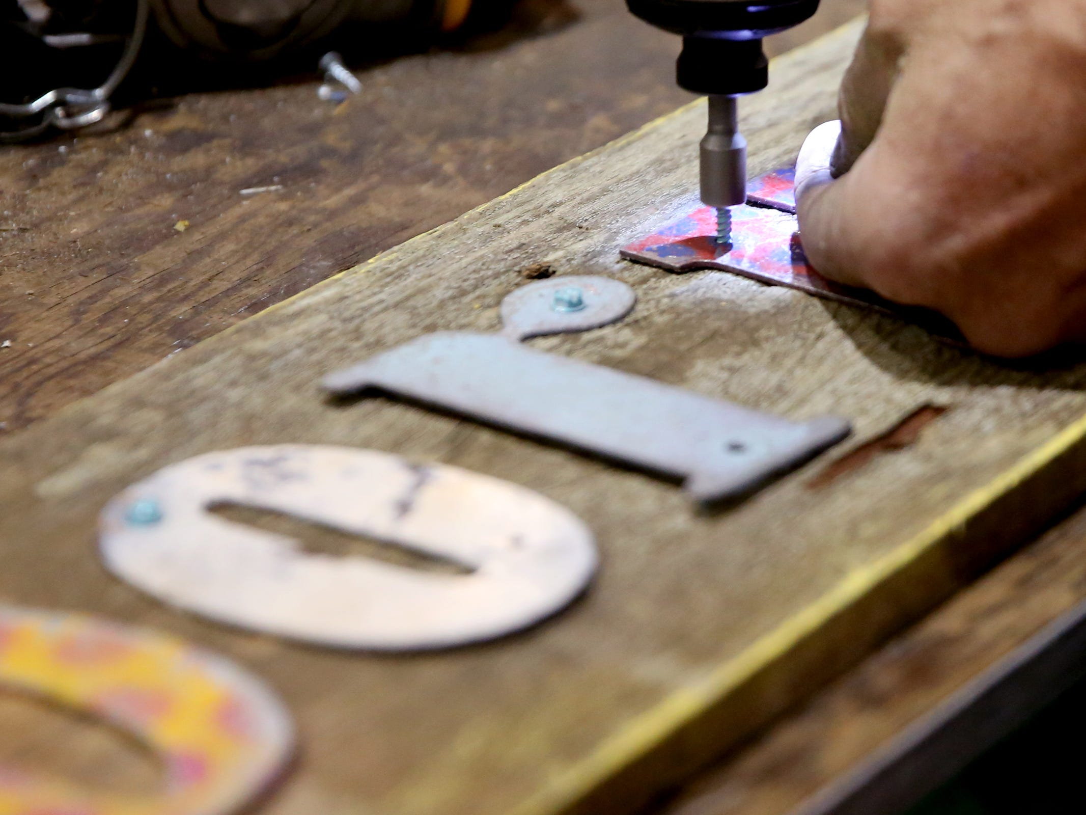 Fred Grandy drills metal letters to a wooden board for a customer during The Great Junk Hunt, a traveling vintage market, at the Oregon State Fairgrounds in Salem on April 13, 2019.