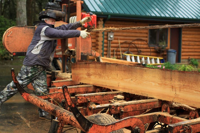 Lee Radtke throws a board while milling timber in Turner. He plans to use the resulting boards to build tables, decorative columns, and other features for Gilgamesh Brewing's new bar in West Salem.
