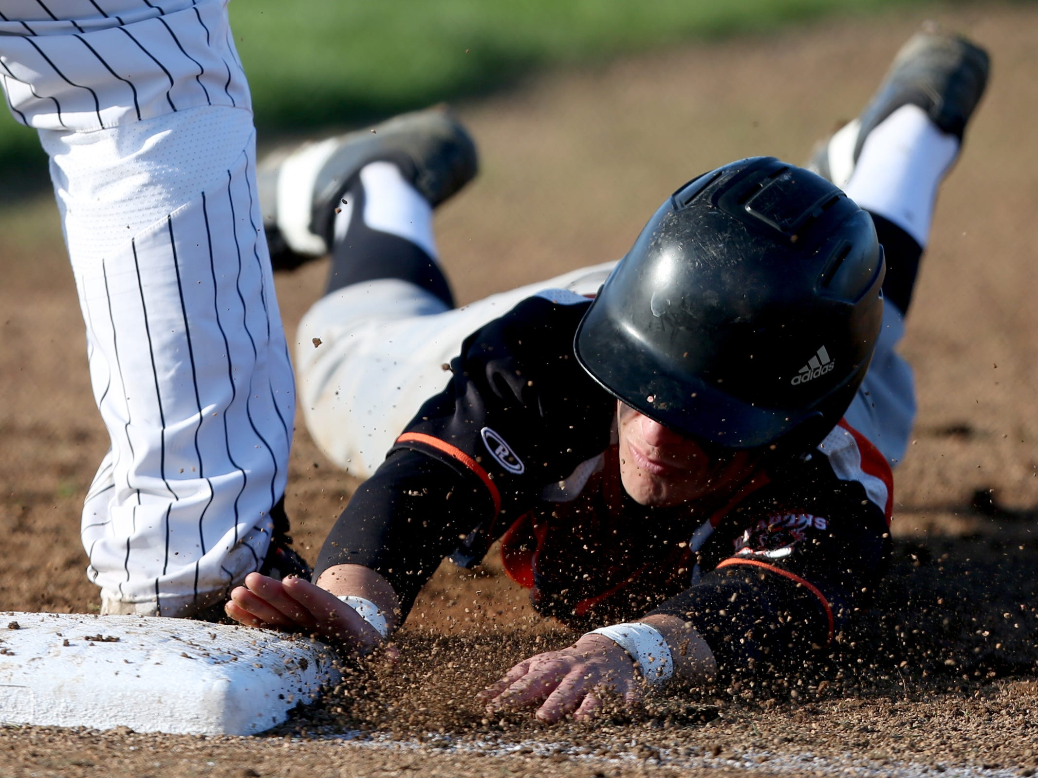 A Dallas player is safe at first after being caught trying to steal in the Dallas vs. North Salem baseball game in Salem on April 12, 2019.