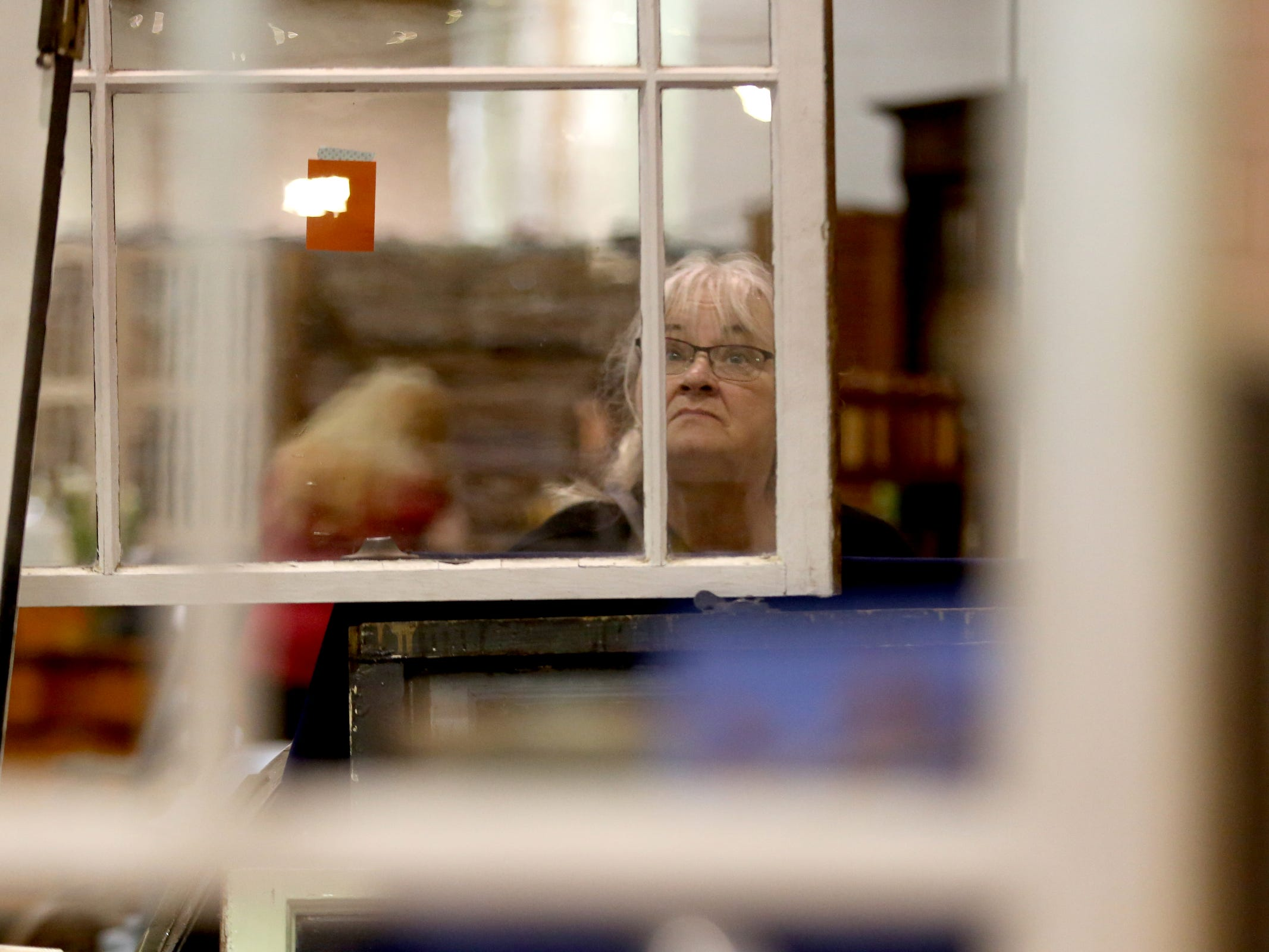 Marilyn Reid, of McMinnville, looks through windows available during The Great Junk Hunt, a traveling vintage market, at the Oregon State Fairgrounds in Salem on April 13, 2019.