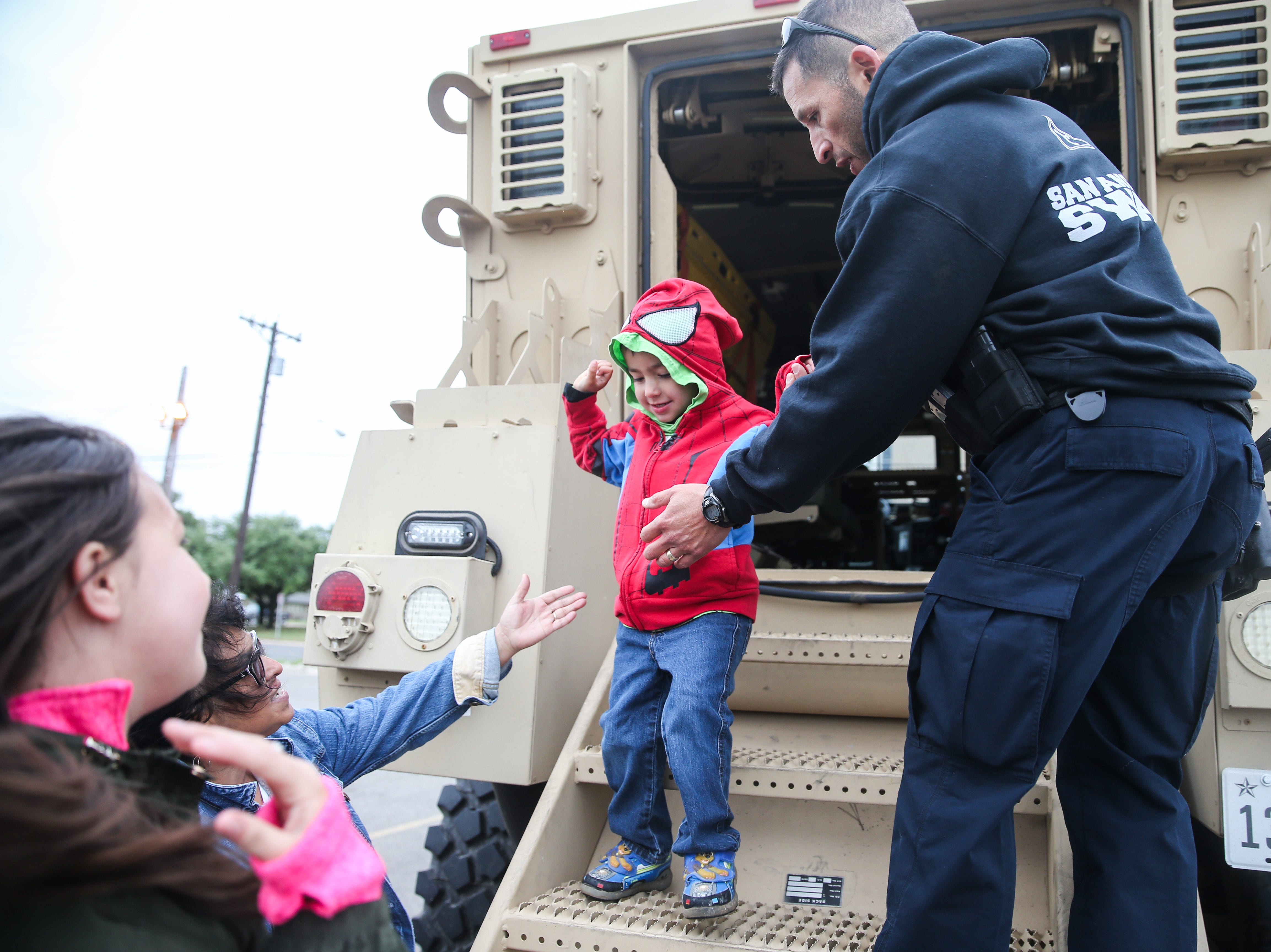Michael Bejil, 3, climbs on a police Swat truck during Touch-a-Truck event Saturday, April 13, 2019, at San Angelo Stadium.