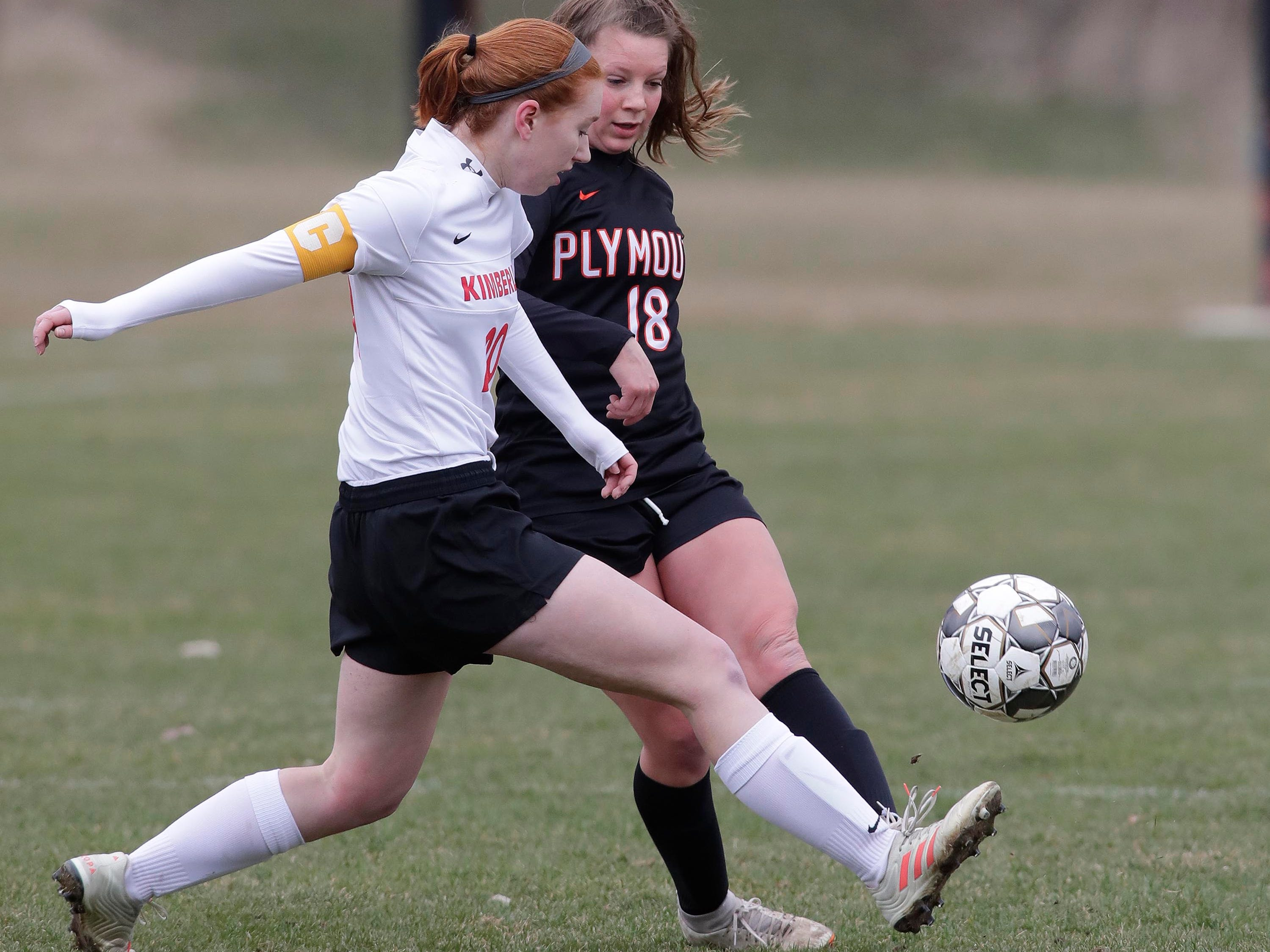 Kimberly's Courtney Rammer (20) controls the ball by Plymouth's Emma Welsch (18), Saturday, April 13, 2019, in Plymouth, Wis.