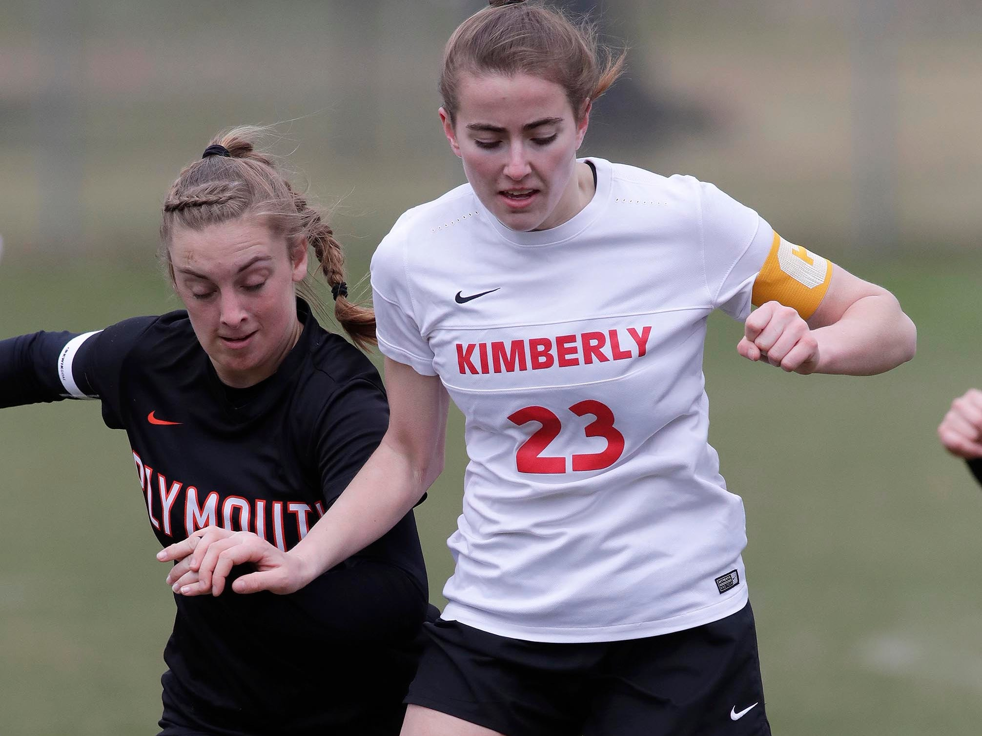 Plymouth's Dallas Kreisa (23, left) and Kimberly's Els Twombly (23) work the ball, Saturday, April 13, 2019, in Plymouth, Wis.