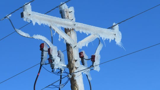 A power pole coated in ice.