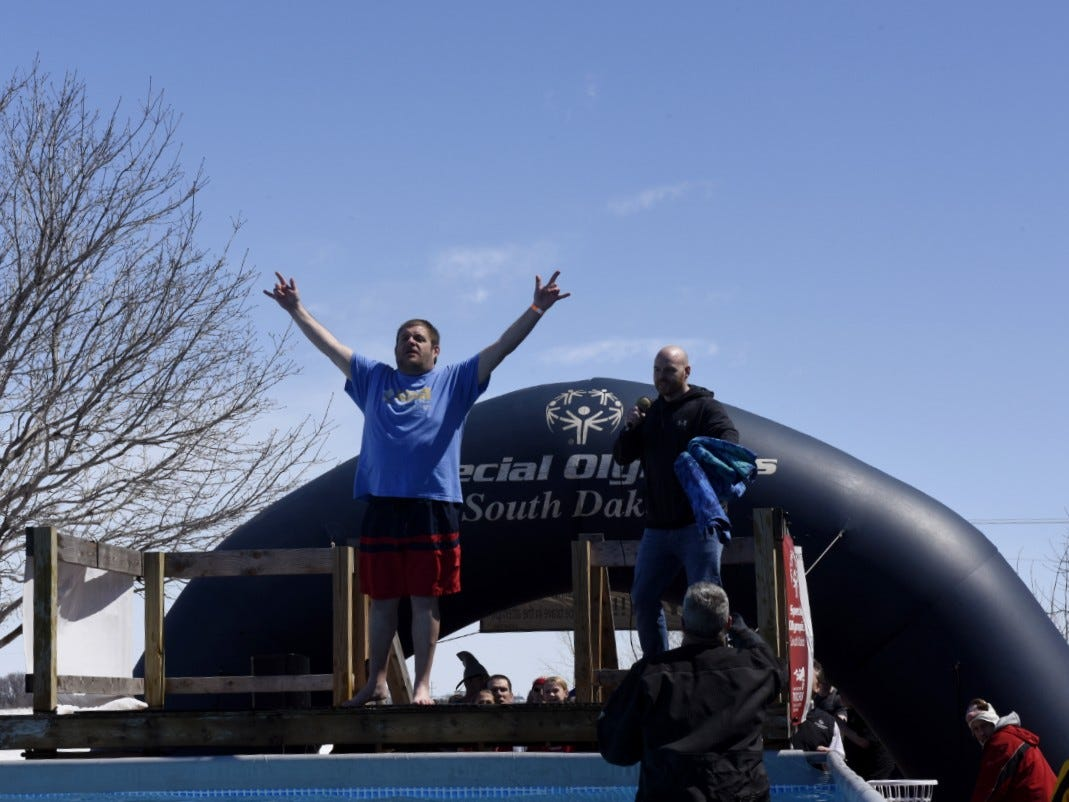 A man raises his hands before jumping into the pool during the Special Olympics South Dakota Polar Plunge at J&L Harley Davidson in Sioux Falls, South Dakota on Saturday, April 13, 2019.