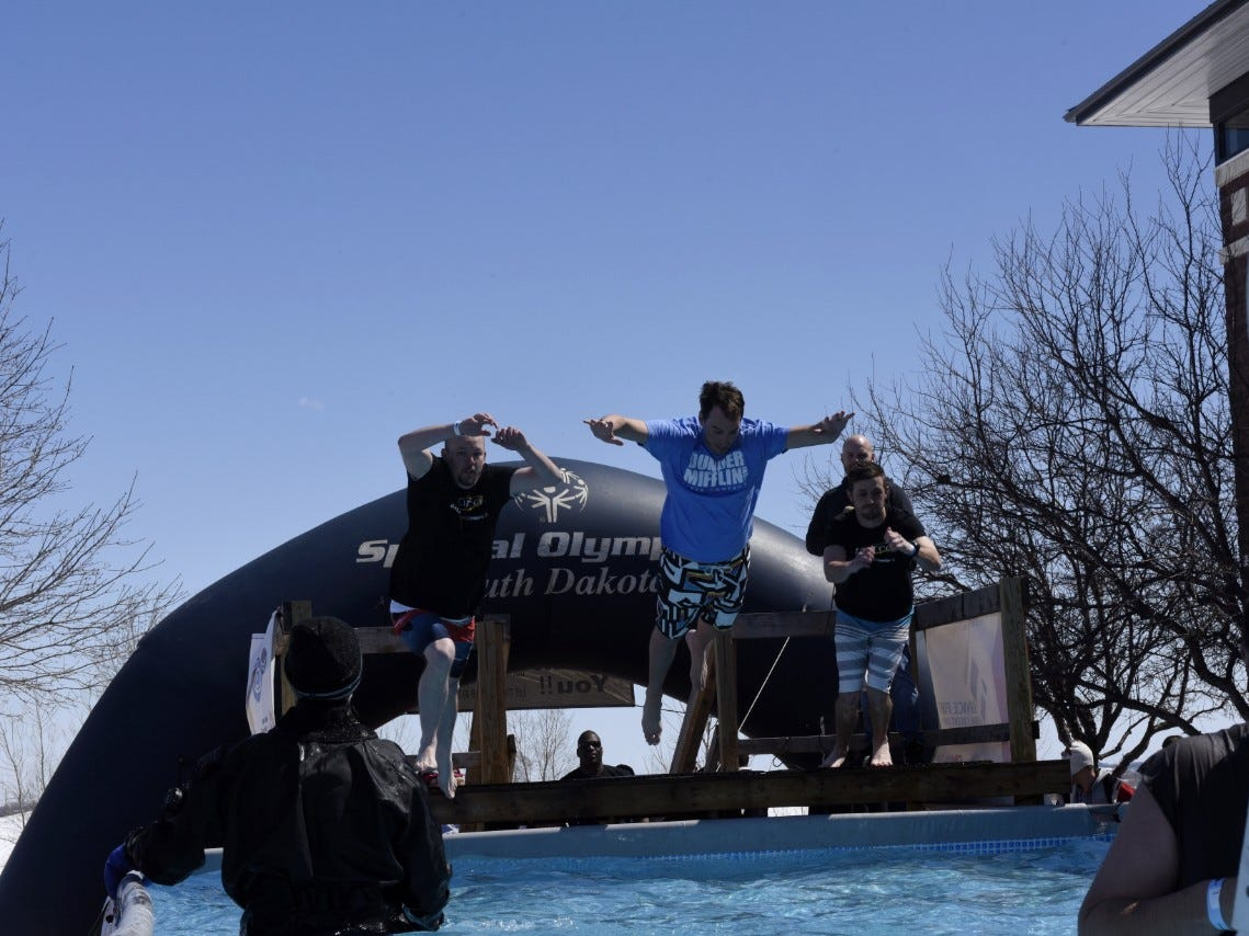 Three men belly flop into the pool during the Special Olympics South Dakota Polar Plunge at J&L Harley Davidson in Sioux Falls, South Dakota on Saturday, April 13, 2019.
