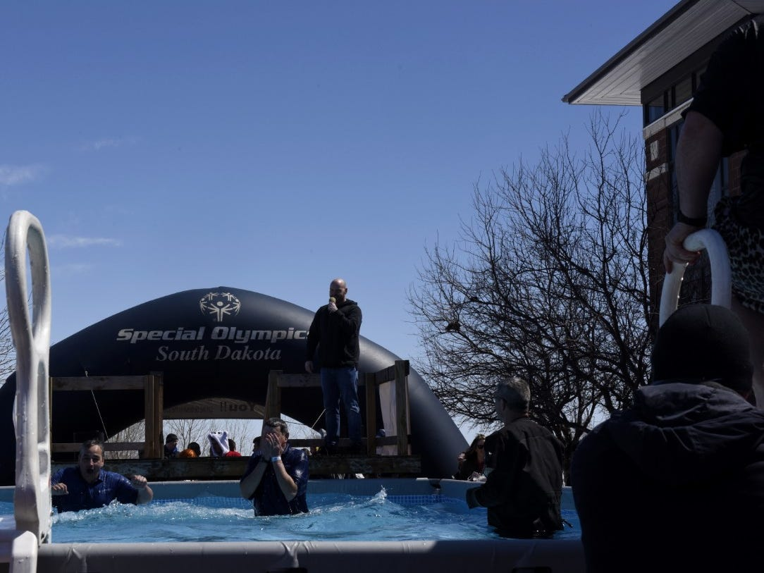 A man wipes his face after jumping into a pool during the Special Olympics South Dakota Polar Plunge at J&L Harley Davidson in Sioux Falls, South Dakota on Saturday, April 13, 2019.