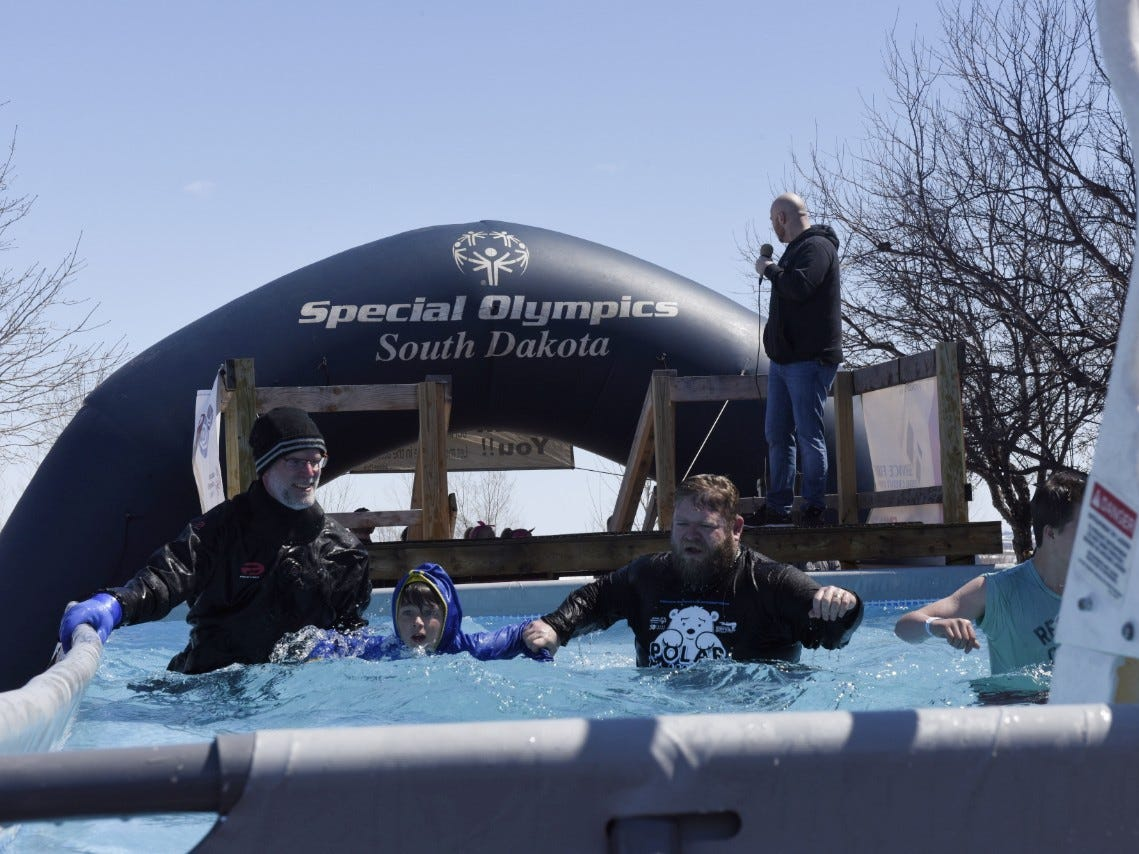 A man and two boys swim toward the ladder of the pool during the Special Olympics South Dakota Polar Plunge at J&L Harley Davidson in Sioux Falls, South Dakota on Saturday, April 13, 2019.