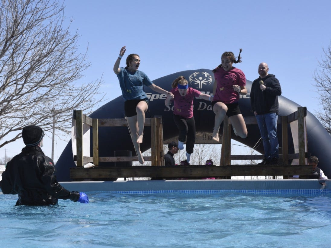 Three girls scream before they jump into ice-cold water during the Special Olympics South Dakota Polar Plunge at J&L Harley Davidson in Sioux Falls, South Dakota on Saturday, April 13, 2019.
