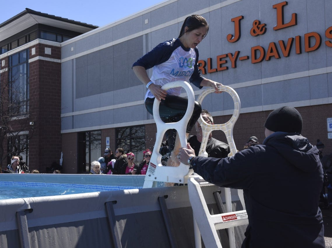 A woman climbs out of the pool after participating in the Special Olympics South Dakota Polar Plunge at J&L Harley Davidson in Sioux Falls, South Dakota on Saturday, April 13, 2019.