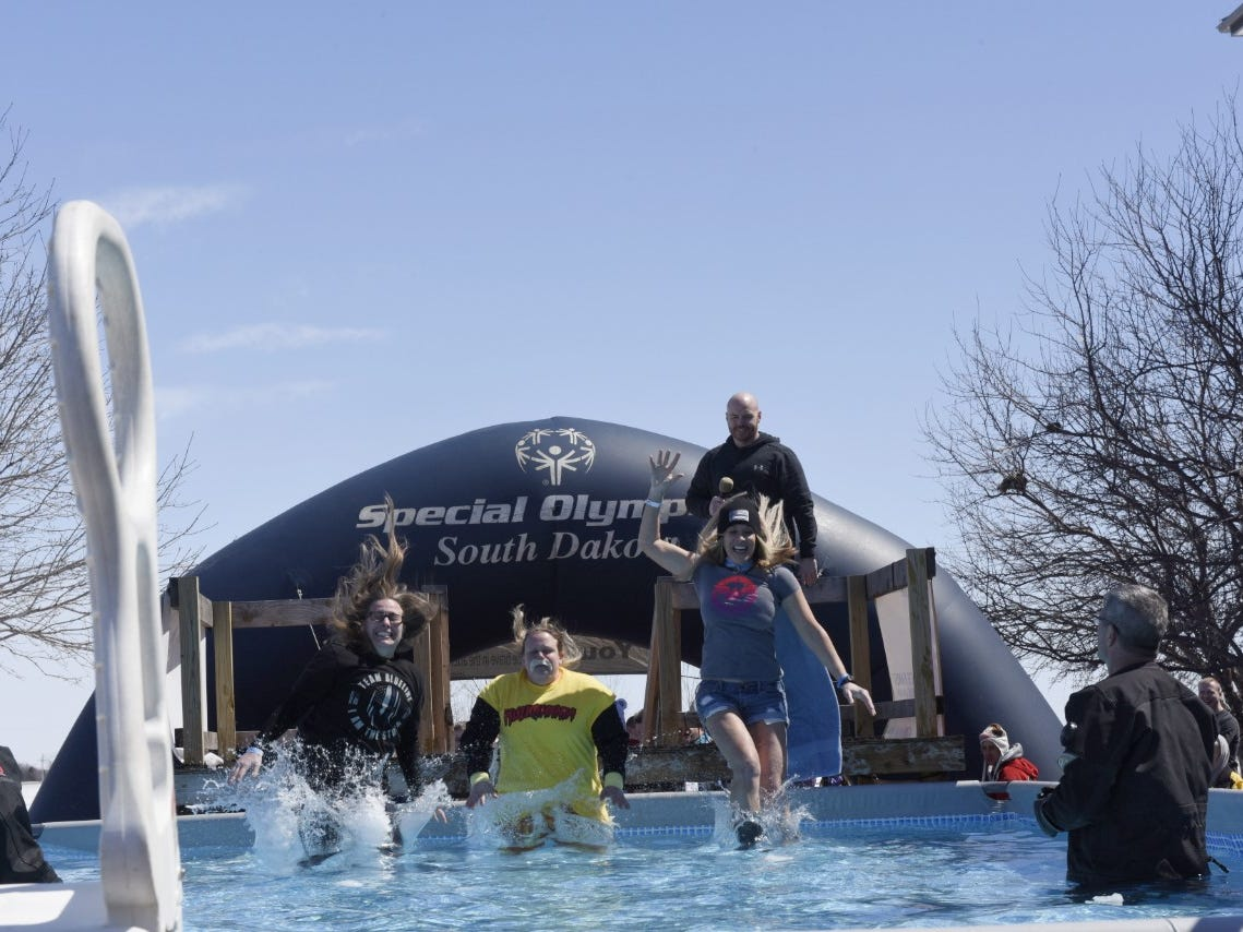 Three women grin as they participate in the Special Olympics South Dakota Polar Plunge at J&L Harley Davidson in Sioux Falls on Saturday, April 13, 2019.