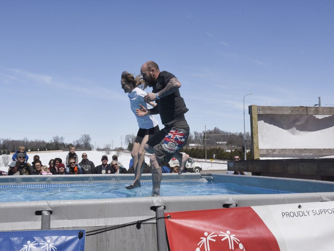 A man and woman jump into the pool during the Special Olympics South Dakota Polar Plunge at J&L Harley Davidson in Sioux Falls, South Dakota on Saturday, April 13, 2019.