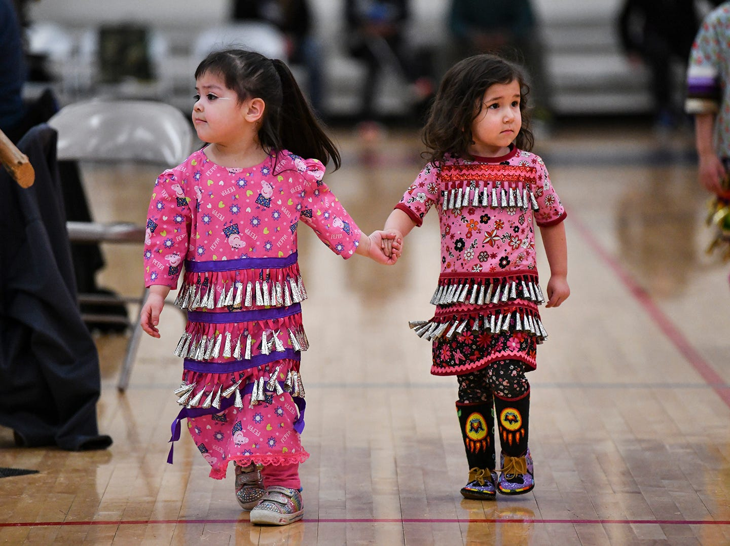 Young dancers in jingle dances join in during a dance at the 25th annual American Indian Center Powwow Saturday, April 13, at Apollo High School in St. Cloud.