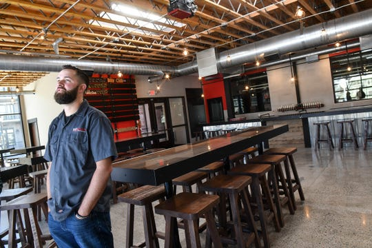Owner Aaron Rieland talks about features of the taproom at the new Bad Habit Brewing Company location Saturday, April 13, in St. Joseph.