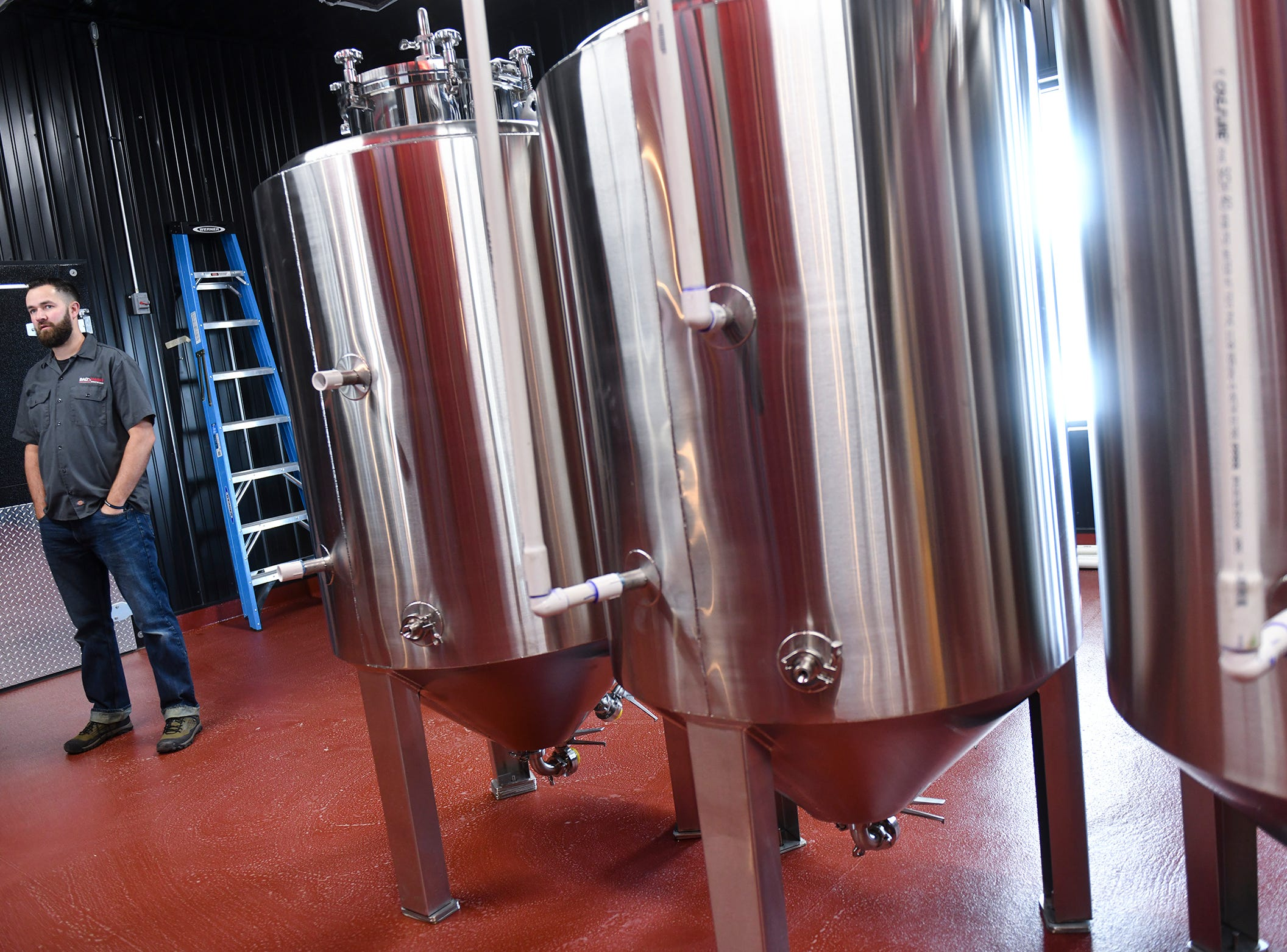 Owner Aaron Rieland talks about new fermentation tanks installed in the brewing area at the new Bad Habit Brewing Company location Saturday, April 13, in St. Joseph.