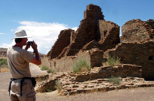 FILE - In this Aug. 10, 2005, file photo, tourist Chris Farthing from Suffolks County, England, takes a picture while visiting Chaco Culture National Historical Park in northwestern New Mexico. Members of New Mexico's congressional delegation are renewing a call for the creation of a formal buffer around the national park held sacred by Native Americans. A measure reintroduced Tuesday, April 9, 2019, would prevent future leasing or development of minerals on federally-owned land within a 10-mile radius of Chaco Culture National Historical Park. (AP Photo/Jeff Geissler, File)