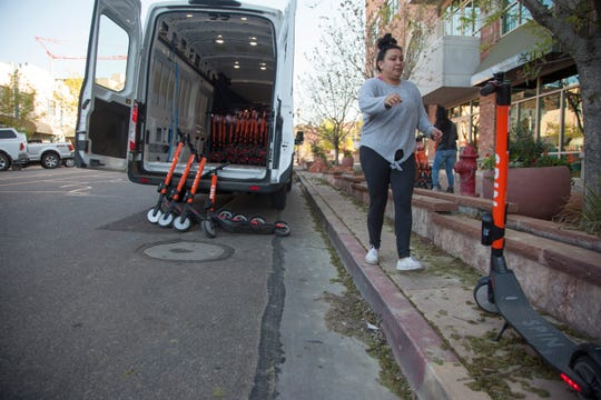 Workers unload Spin scooters in downtown St. George Saturday, April 6, 2019.