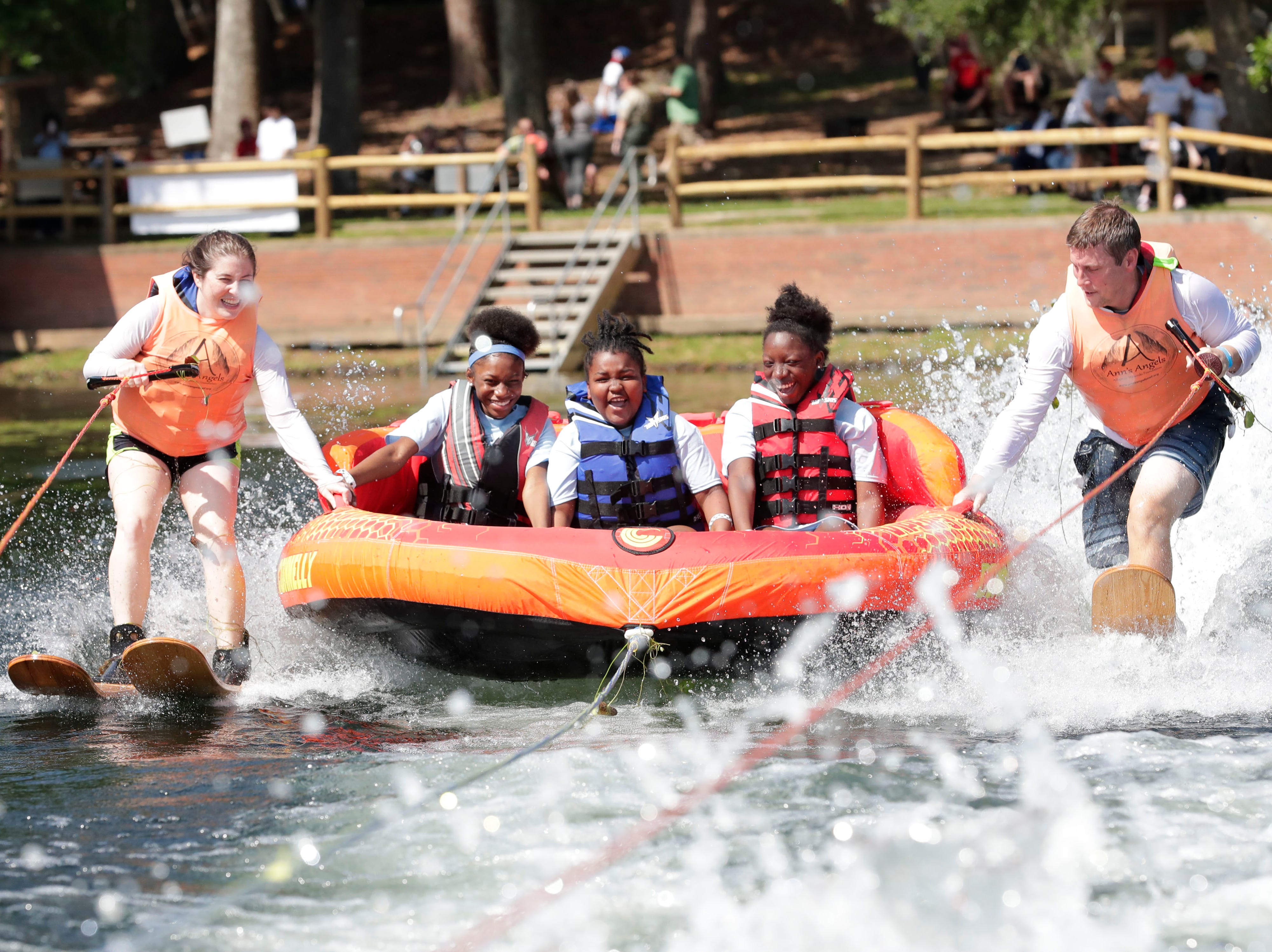 De'Ayja Arnett, 14, second from left, Adrian Gordon, 8, and Destyne Arnett, 12, tube on the water during SportsAbility, a program with the Florida Disabled Outdoors Association, at Maclay Garden State Park Saturday,  April 13, 2019.
