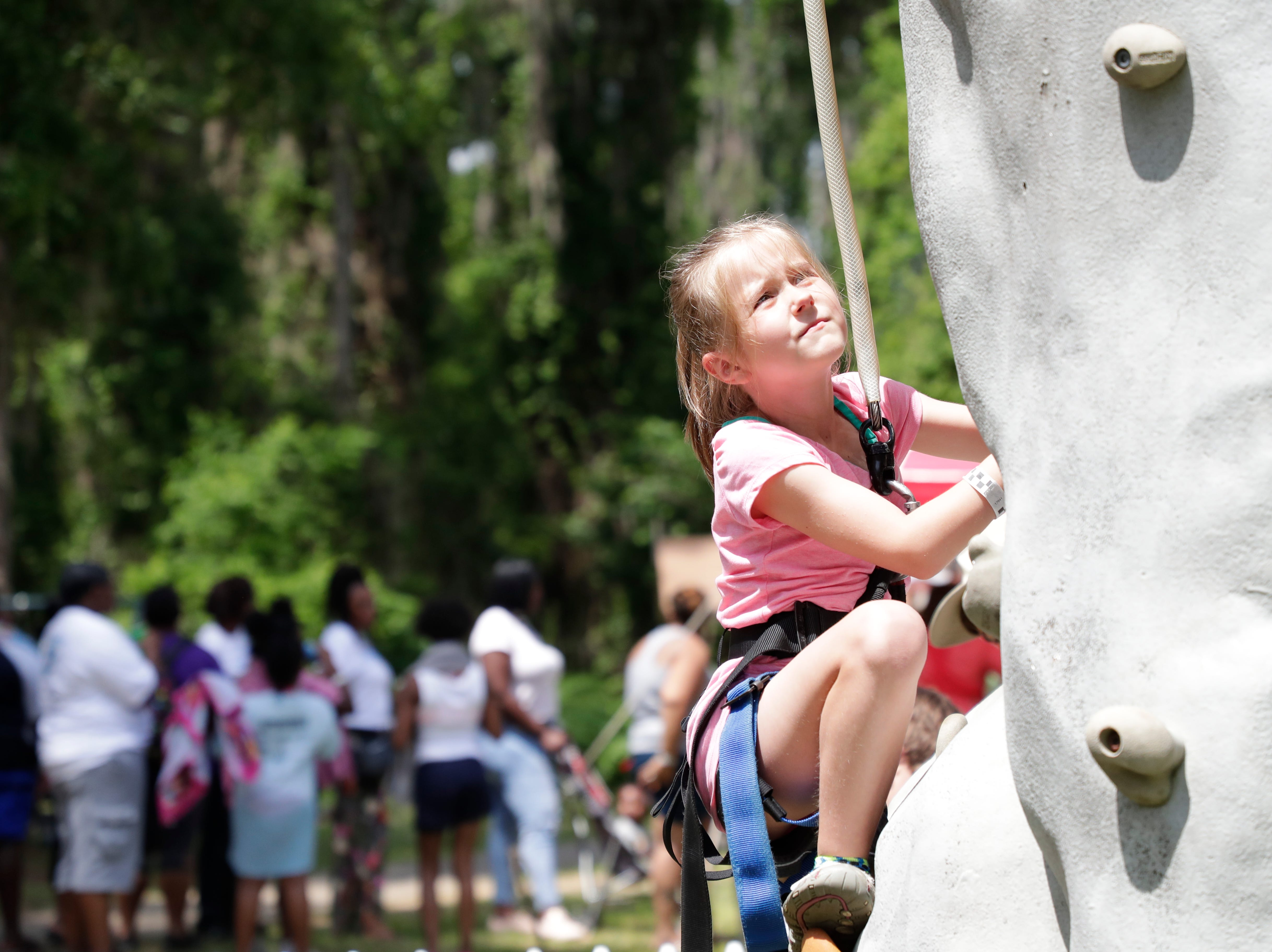 Chris Barfield, 7, climbs the rock wall during SportsAbility, a program with the Florida Disabled Outdoors Association, at Maclay Garden State Park Saturday,  April 13, 2019.