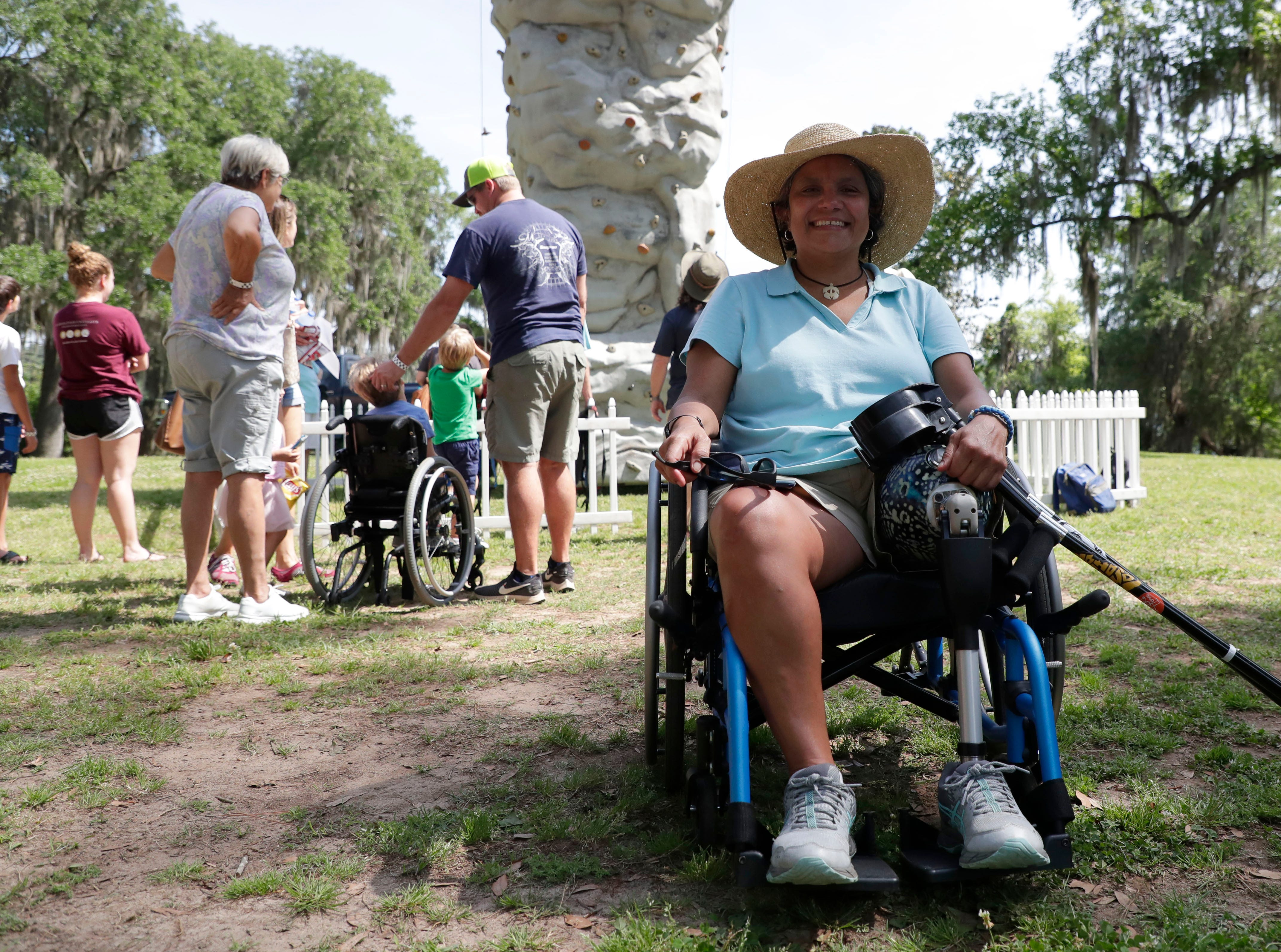 Mariela Mason poses for a photo in front of the rock wall she just conquered during SportsAbility, a program with the Florida Disabled Outdoors Association, at Maclay Garden State Park Saturday,  April 13, 2019.