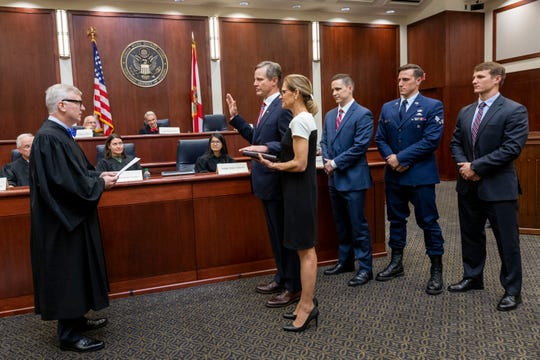 Lawrence Keefe, second from left, is joined by his wife Dr. Lynn Keefe and sons Robert, John and Patrick, right, as he takes the Oath of Office as the United States Attorney for the Northern District of Florida from Mark Walker, left, chief United States district judge on Friday. COLIN HACKLEY PHOTO