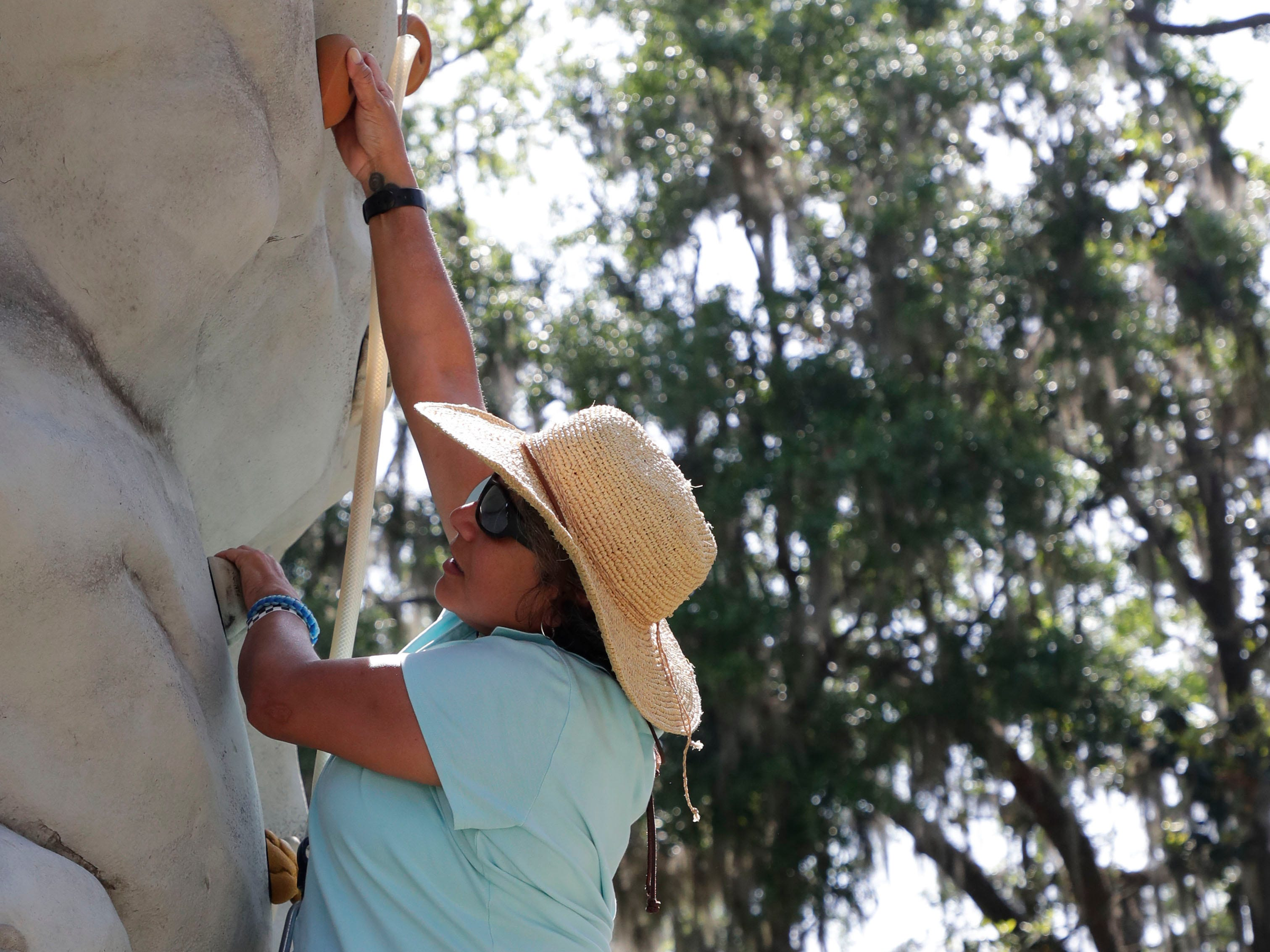 Mariela Mason climbs the rock wall during SportsAbility, a program with the Florida Disabled Outdoors Association, at Maclay Garden State Park Saturday,  April 13, 2019.