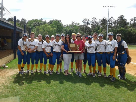 Members of the 2019 softball team at Tallahassee Community College pose as Kelly Best Hale (left) and Windy Taff Jones show off the 1994 NJCAA softball championship trophy on Friday, April 12, 2019.