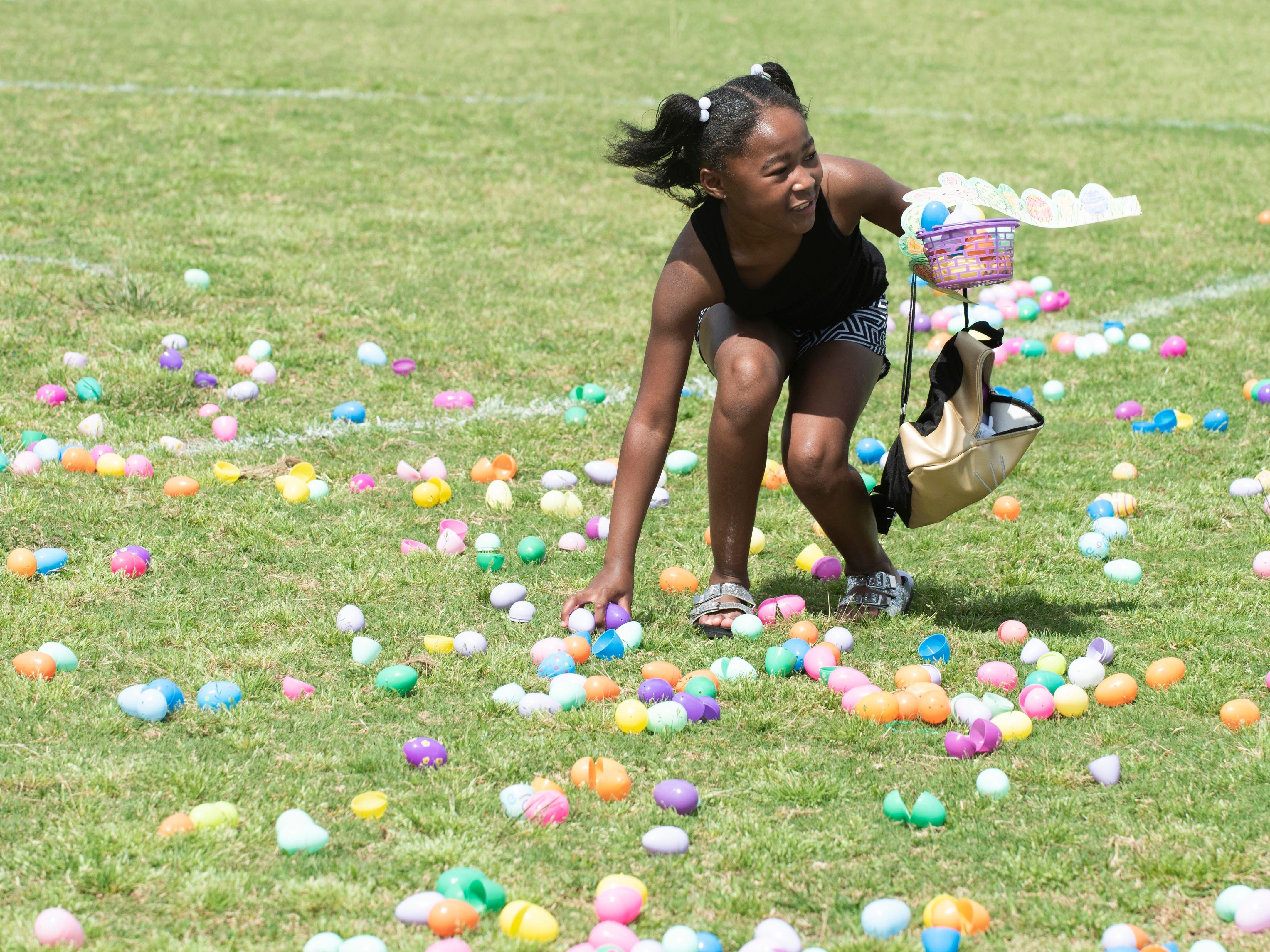 """Elaine Witt, 10, of Stuart, picks up plastic eggs during the Spring Community Mixer and Egg Hunt on Saturday, April 13, 2019, at the 10th Street Community Center Guy Davis Sports Complex in Stuart. The hunt was divided into four, separate age groups. Children picked up the eggs and traded them in for bags of candy.  """"It's nice to do these things around the holidays to get the community out and give them a free event to enjoy with their family and a place where they can meet other members of the community and learn what's going in their area,"""" said Jessica Tharp, not pictured, the recreation program supervisor for the City of Stuart and the organizer of the event. The mixer also included golden eggs, face painting, carnival games, inflatables and free popcorn, snow cones and a hot dog lunch."""