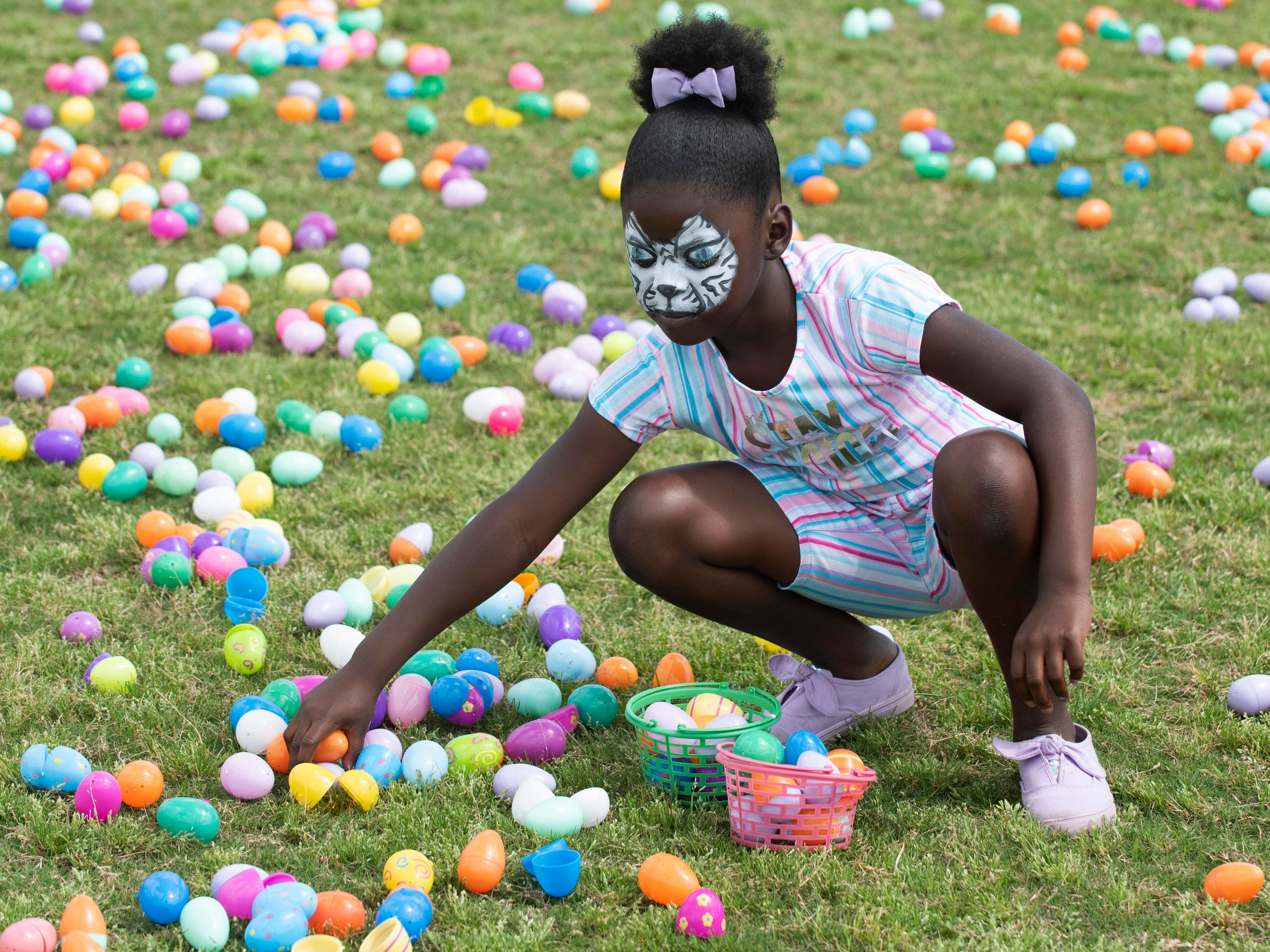 """Rhylie Straughter, 7, of Stuart, picks up plastic eggs during the Spring Community Mixer and Egg Hunt on Saturday, April 13, 2019, at the 10th Street Community Center Guy Davis Sports Complex in Stuart. The hunt was divided into four, separate age groups. Children picked up the eggs and traded them in for bags of candy.  """"It's nice to do these things around the holidays to get the community out and give them a free event to enjoy with their family and a place where they can meet other members of the community and learn what's going in their area,"""" said Jessica Tharp (not pictured), the recreation program supervisor for the City of Stuart and the organizer of the event. The mixer also included golden eggs, face painting, carnival games, inflatables and free popcorn, snow cones and a hot dog lunch."""