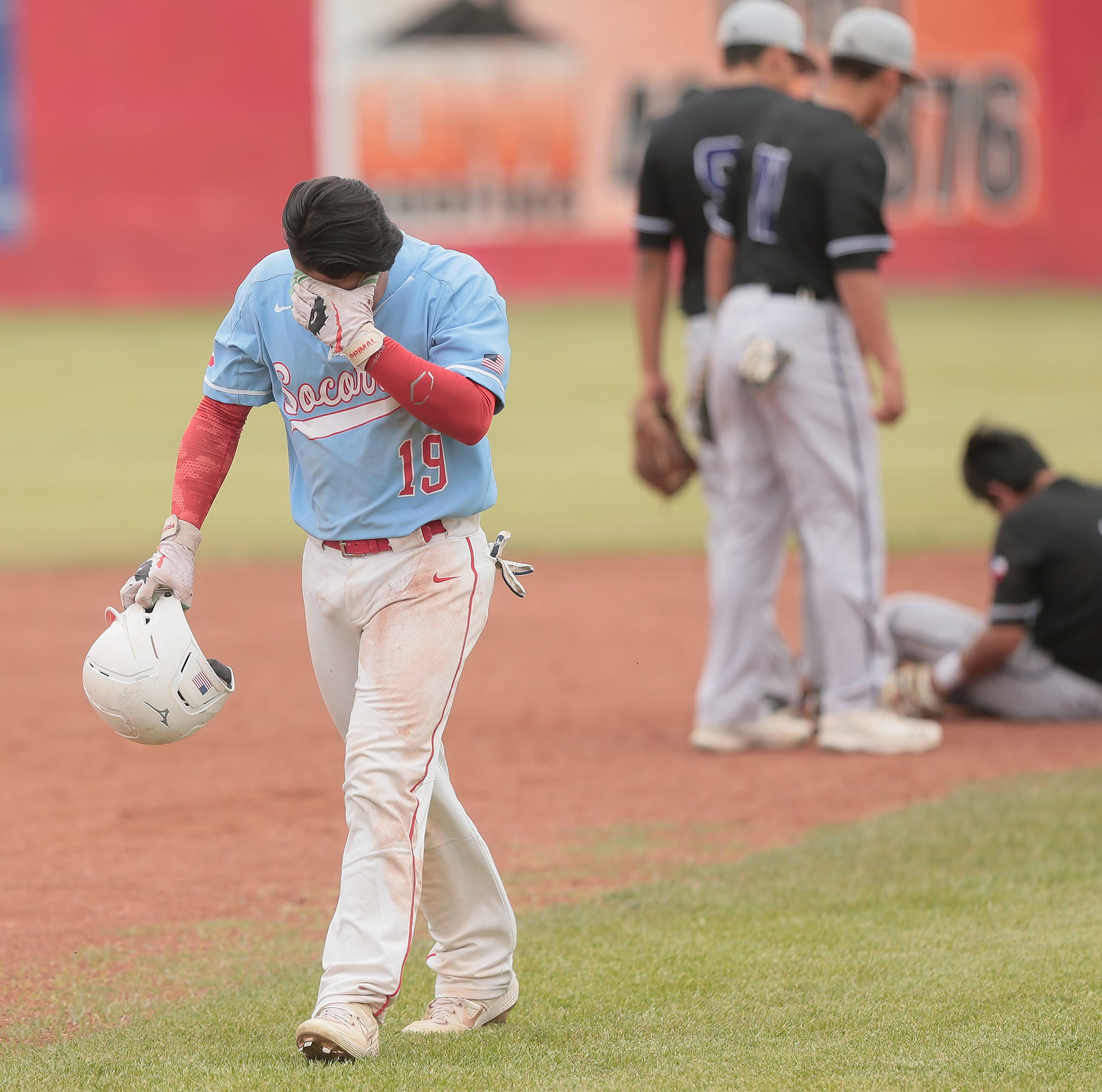 Socorro base runner Gerardo Contreras walks back to the dugout shook up after colliding with Franklin second baseman Eddie Rodriguez Friday.