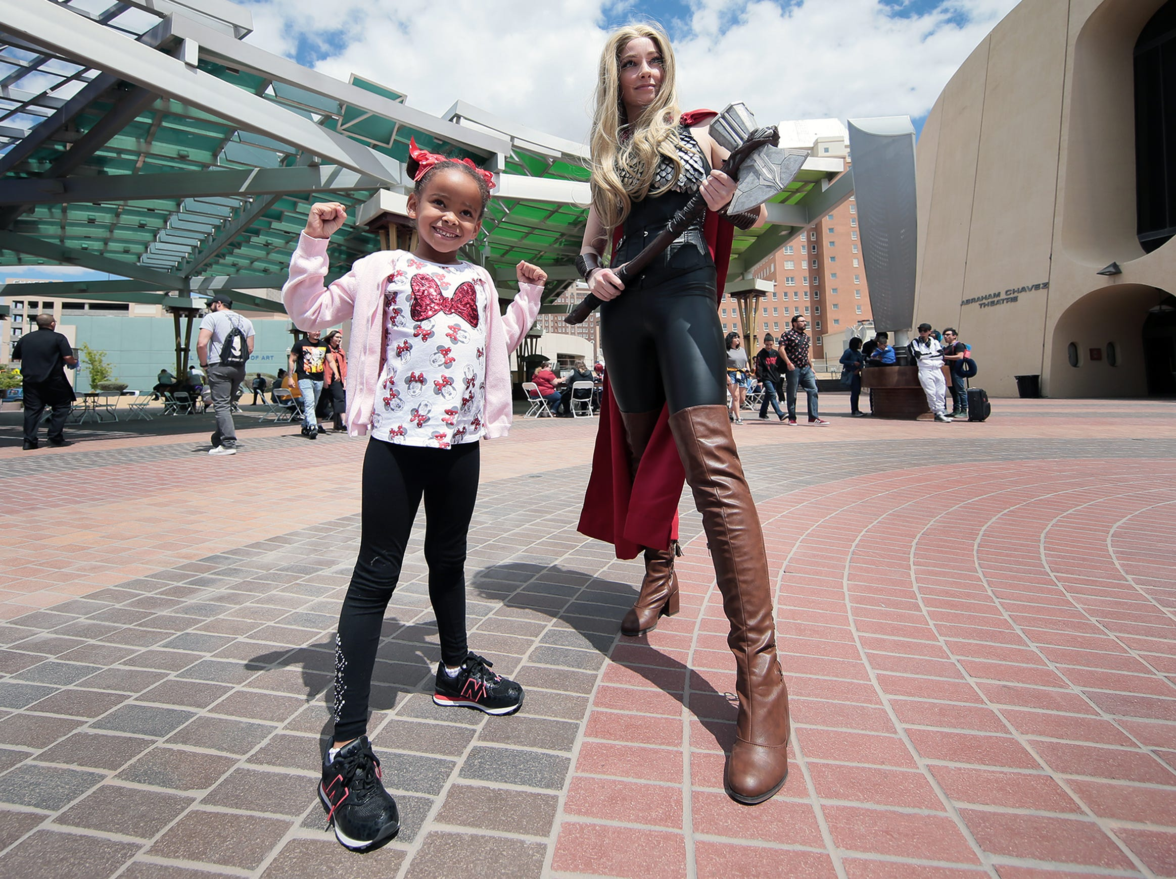 A young fan flexes as she takes a photo with Kosmic Kenna outside the El Paso convention center on Saturday, April 13, 2019. El Paso Comic Con continues Sunday.