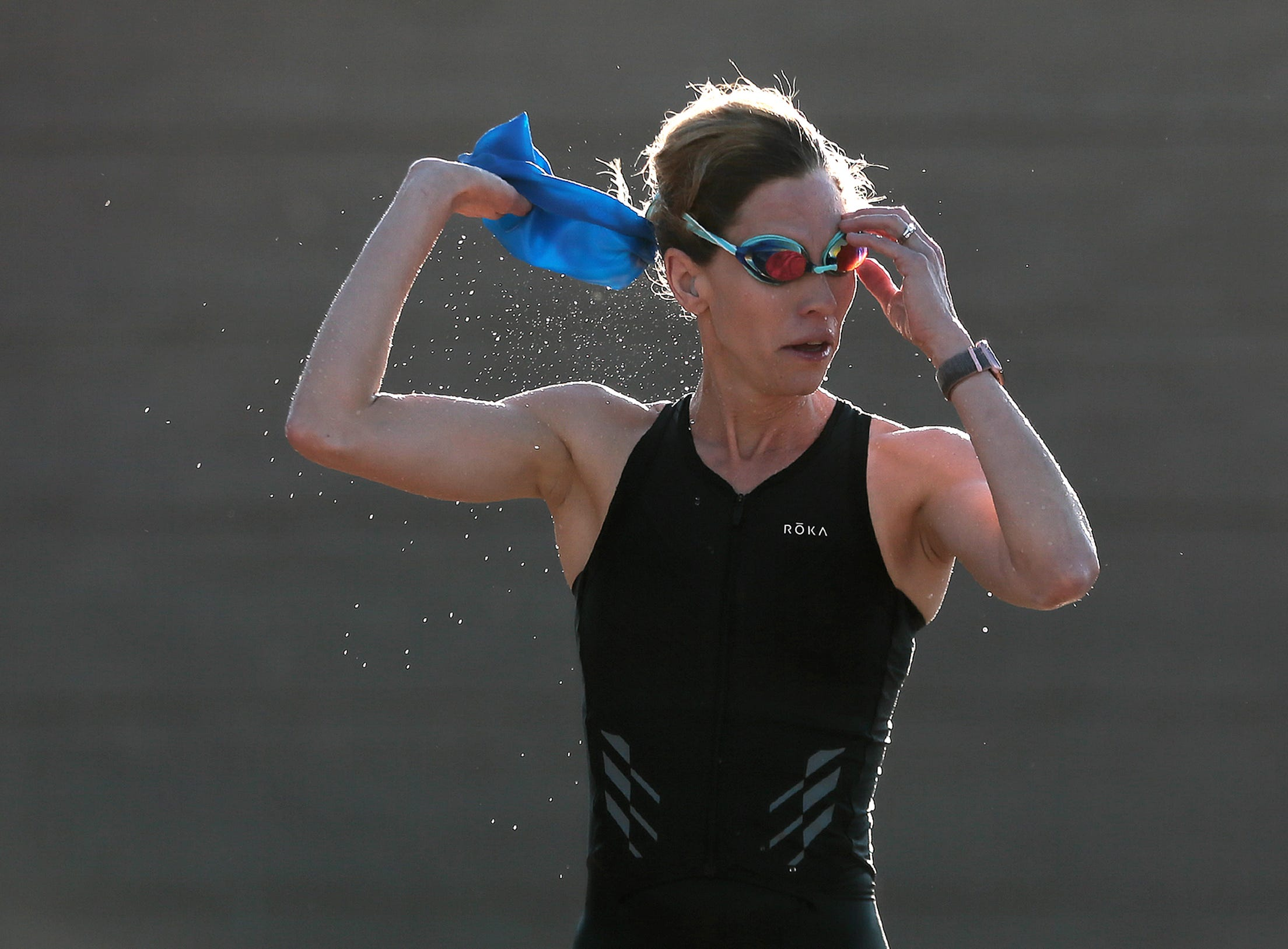 A triathlete rips off her cap and goggles after the swim portion of the Mighty Mujer Triathlon Saturday at Memorial Park Pool.