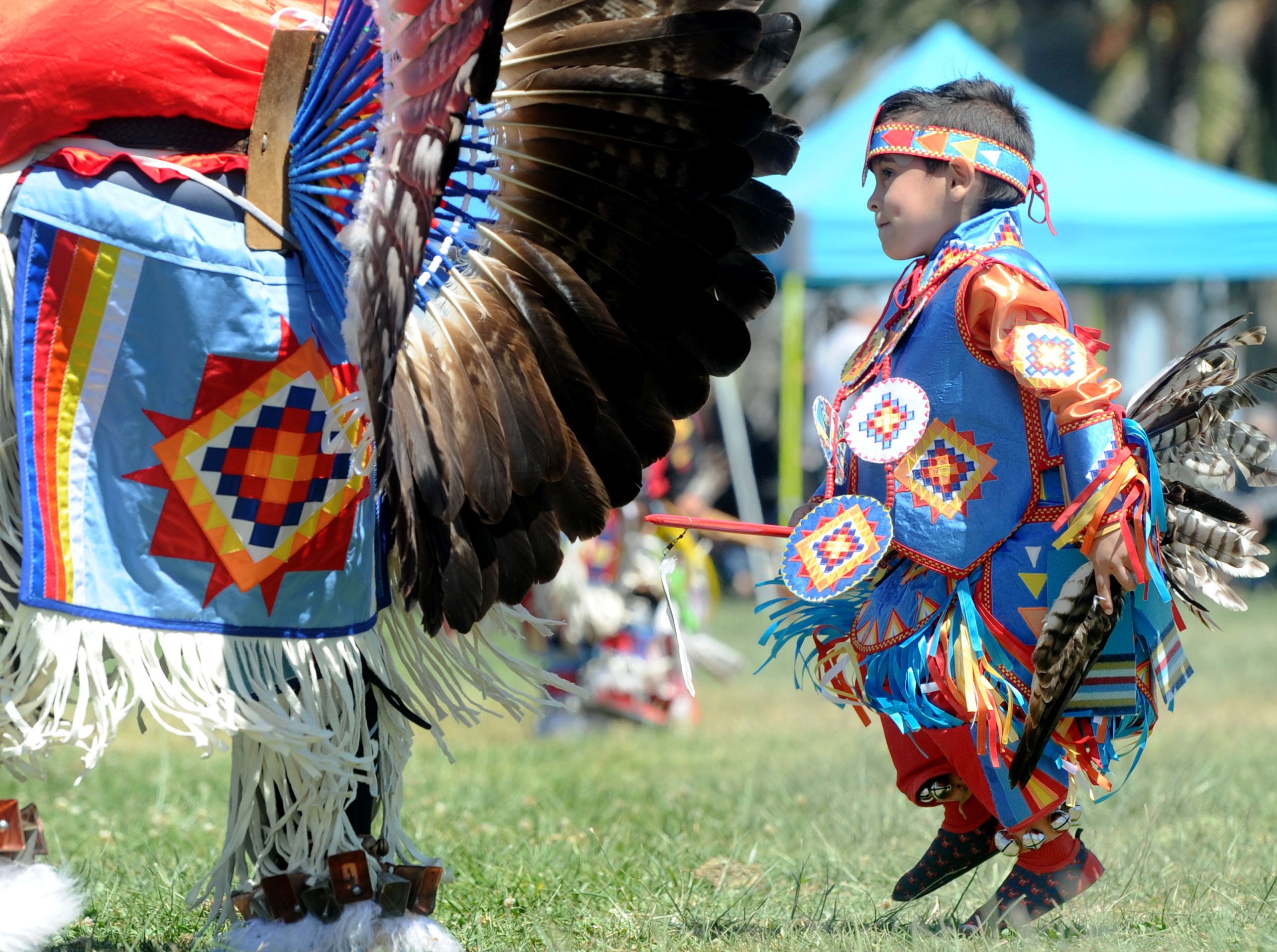 """Steven Gonzales, of Bakersfield, dances with his father, Tommy Gonzales, on Saturday during the intertribal powwow at Oxnard Beach Park. The theme was """"Honoring Our Elders and Veterans."""""""