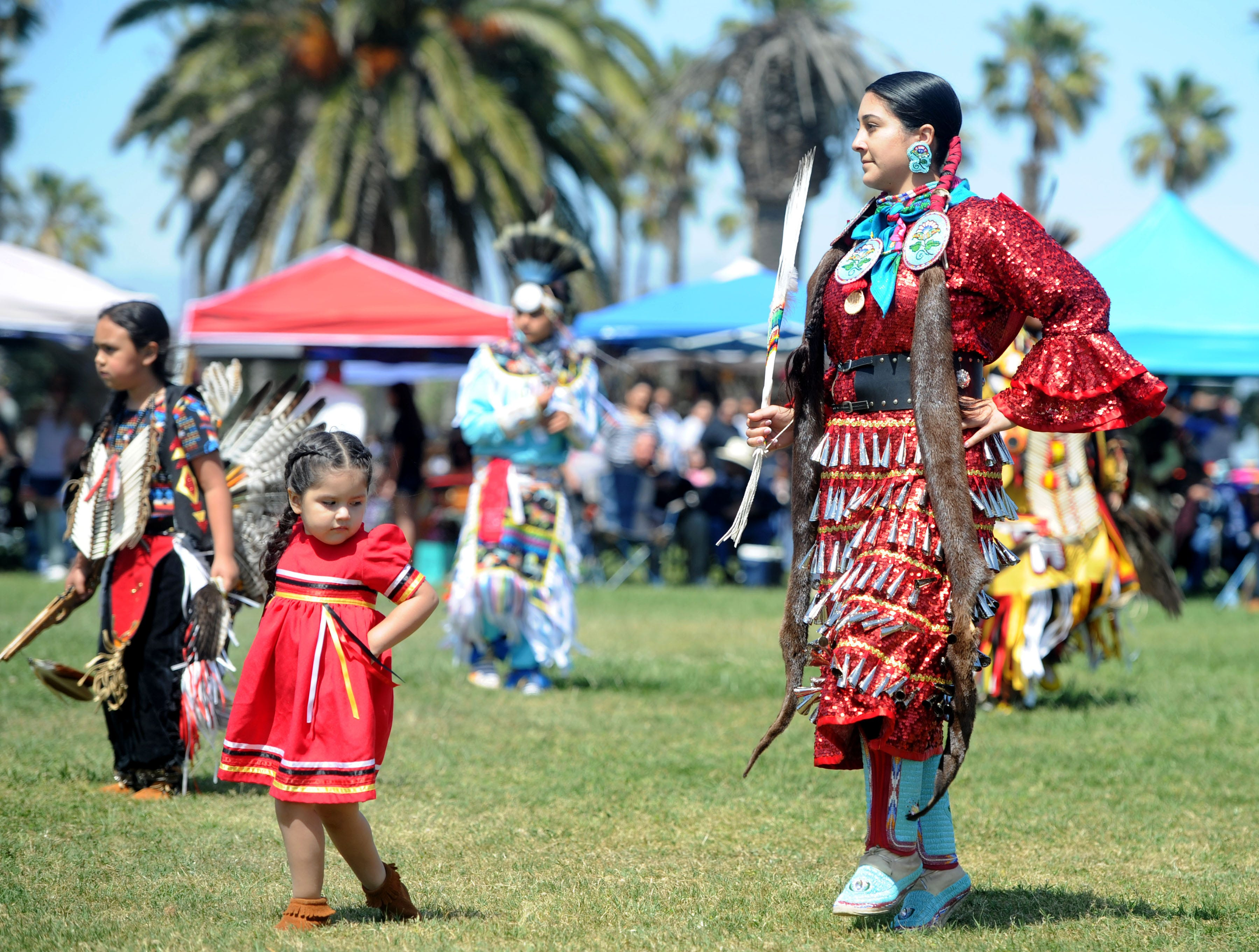 """Helena Ramirez watches Monica Jacome dance during the intertribal powwow at Oxnard Beach Park. The theme was """"Honoring Our Elders and Veterans."""""""