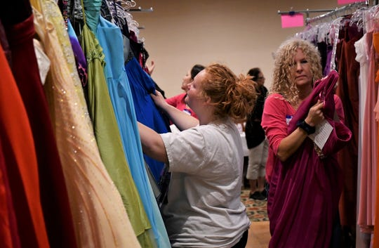 Sarah Gibbs, a junior at Visalia Technical Early College High School, looks for a dress during Enchanted Evening's annual prom dress giveaway. The event was held on Saturday, April 13 at the Wyndham Hotel in Visalia.