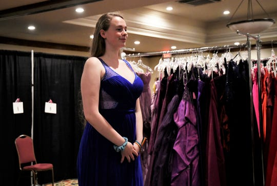 Ashley Casper, a senior at Tulare Western High School, tries on a dress during Enchanted Evening's annual prom dress giveaway. The event was held on Saturday, April 13 at the Wyndham Hotel in Visalia.