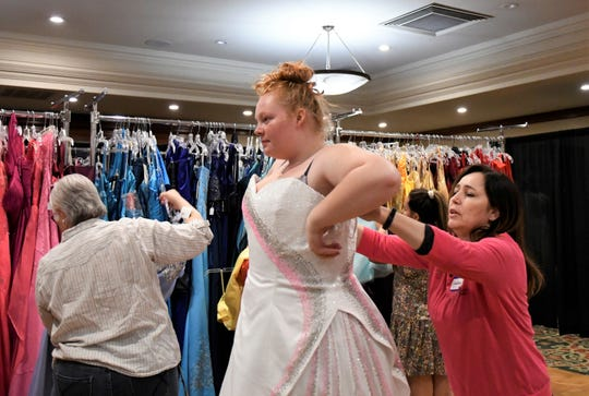 Sarah Gibbs, a junior at Visalia Technical Early College High School, tries on a dress during Enchanted Evening's annual prom dress giveaway. The event was held on Saturday, April 13 at the Wyndham Hotel in Visalia.