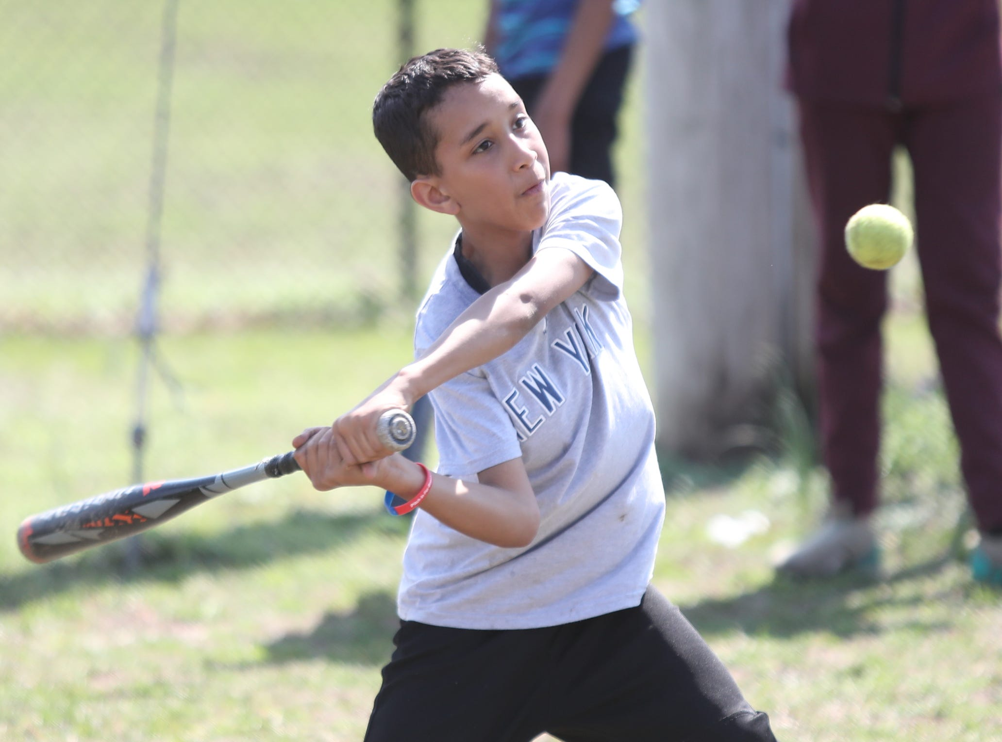 Joan Pau, 11, takes a swing at a pitch during little league practice at Brush Park on Saturday, April 13, 2019 during Jackie Robinson Day in Mount Vernon.