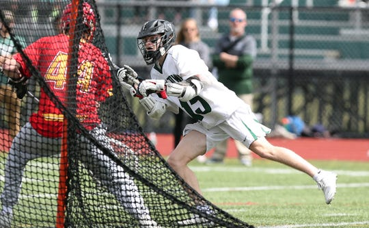 Yorktown's Tim O'Callaghan (15 ) fires a shot that is blocked by Chaminade goalie Liam Entenmann (44) during boys lacrosse action at Yorktown High School April 13,  2019. Chaminade won the game 11-5.