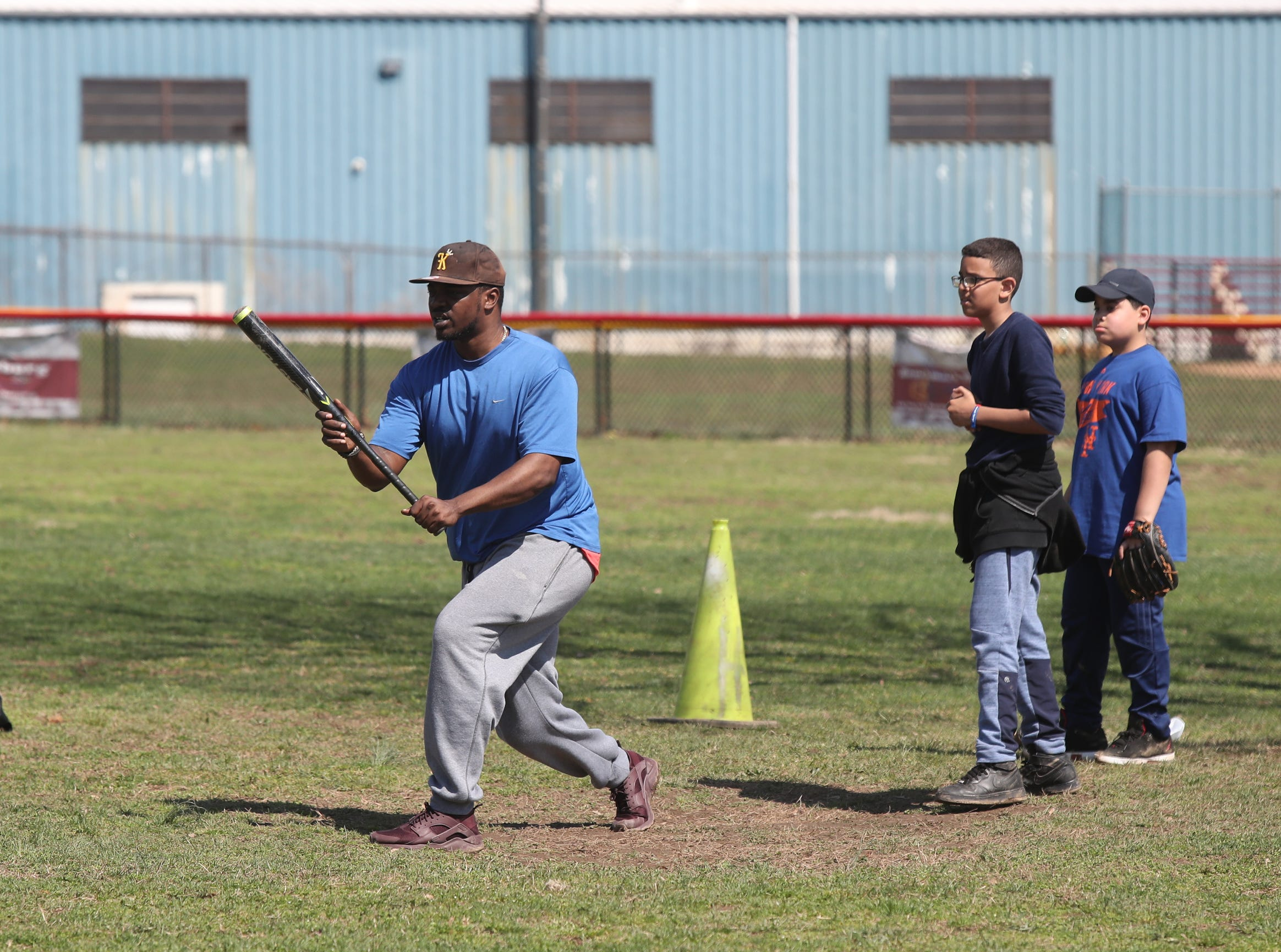 Coach Lawrence Taylor instructs a player on laying down a bunt during little league practice annual Jackie Robinson Day  at Brush Park on Saturday, April 13, 2019.