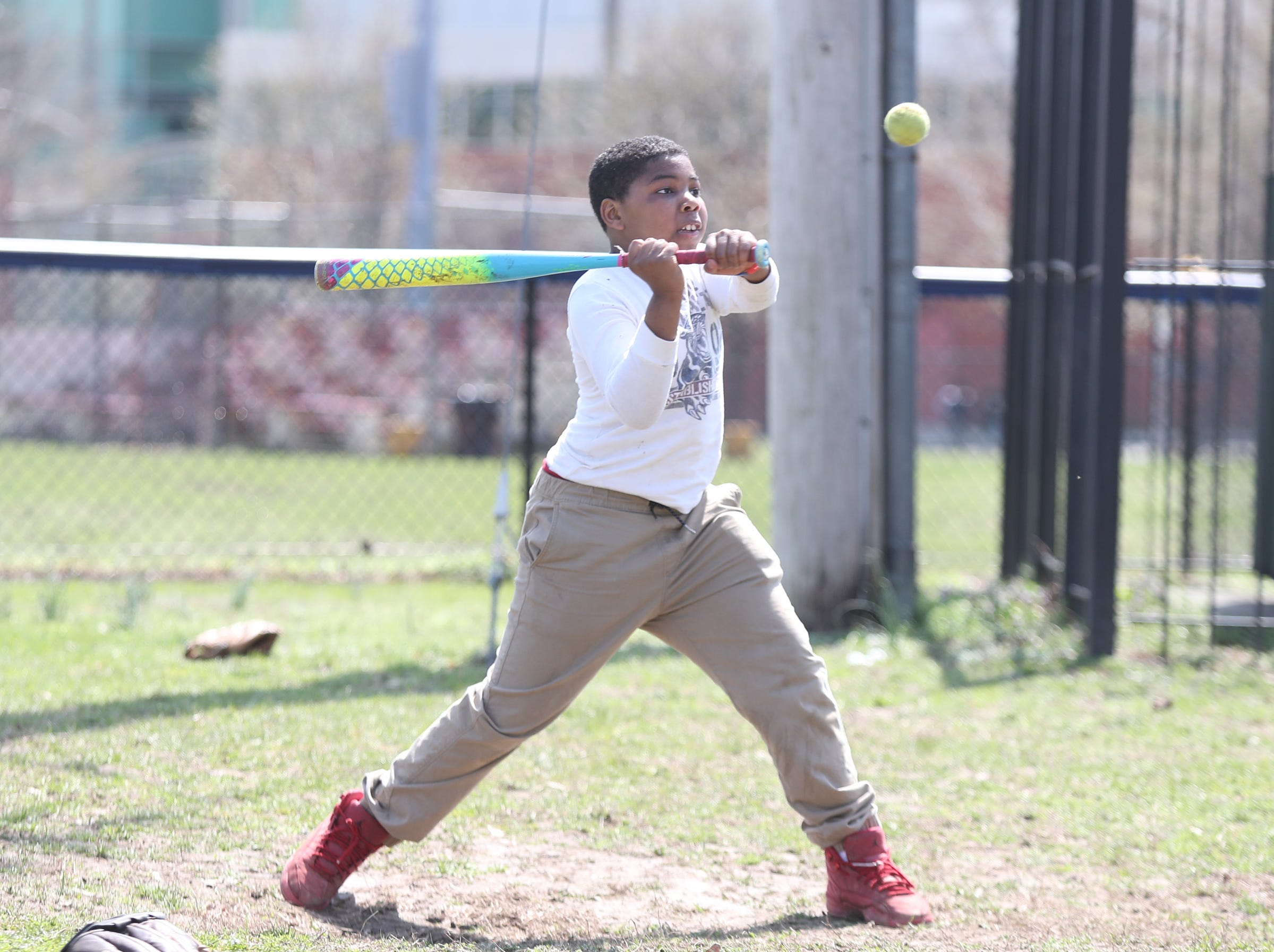 Tarik Shell, 11, takes a swing at a pitch during little league practice at Brush Park on Saturday, April 13, 2019 during Jackie Robinson Day in Mount Vernon.