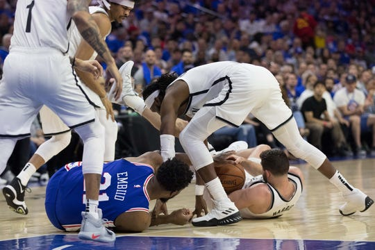 Philadelphia 76ers center Joel Embiid (21) and Brooklyn Nets forward Joe Harris (12) and center Jarrett Allen (31) and forward DeMarre Carroll (9) scramble on the floor for a loose ball during the first quarter in game one of the first round of the 2019 NBA Playoffs at Wells Fargo Center in Philadelphia on Saturday, April 13, 2019.