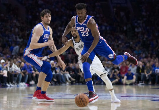 Philadelphia 76ers guard Jimmy Butler (23) dribbles past Brooklyn Nets guard Spencer Dinwiddie (8) during the first quarter in game one of the first round of the 2019 NBA Playoffs at Wells Fargo Center in Philadelphia on Saturday, April 13, 2019.