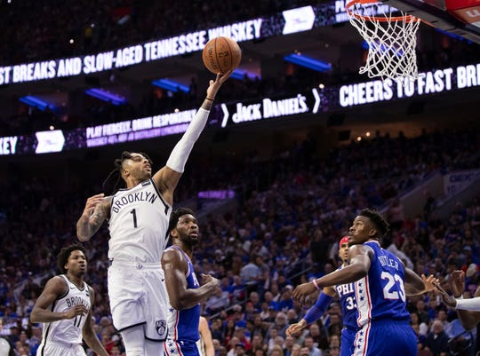 Brooklyn Nets' D'Angelo Russell, left, goes up for the shot as he gets past Philadelphia 76ers' Joel Embiid, center, of Cameroon, during the second half in Game 1 of a first-round NBA basketball playoff series, Saturday, April 13, 2019, in Philadelphia. The Nets won 111-102.