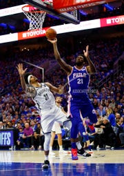 Philadelphia 76ers' Joel Embiid, right, puts up a shot as he is fouled by Brooklyn Nets' Jarrett Allen, left, during the first half in Game 1 of a first-round NBA basketball playoff series, Saturday, April 13, 2019, in Philadelphia. (AP Photo/Chris Szagola)
